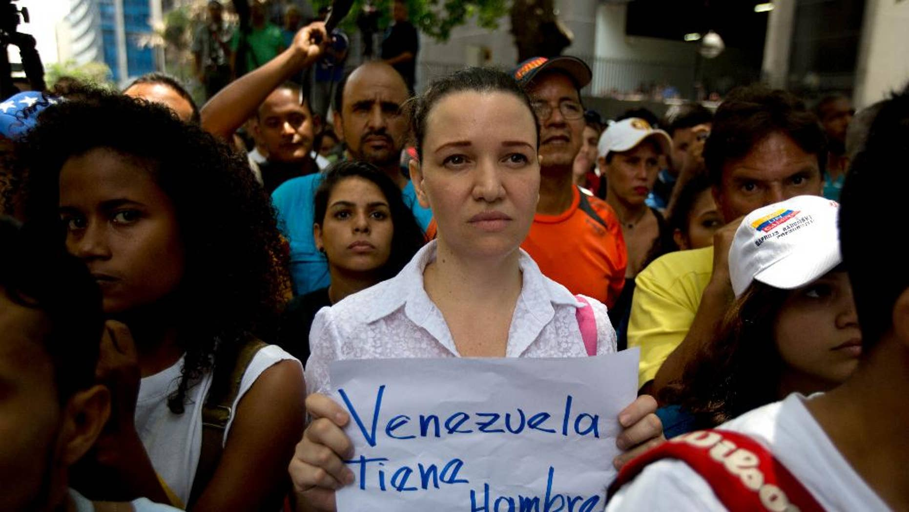 """An opposition members holds a handwritten message that that reads in Spanish; """"Venezuela is hungry,"""" during a protest outside the court offices of the Chacao municipality, in Caracas, Venezuela, Wednesday, May 25, 2016. Opposition members held a demonstration to demand authorities hold a recall referendum on cutting short Nicolas Maduro's presidency. (AP Photo/Fernando Llano)"""
