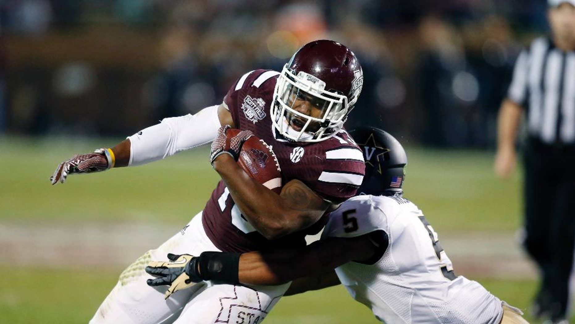 Mississippi State running back Josh Robinson (13) is tackled by Vanderbilt defensive back Torren McGaster (5) after a run for a first down in the first half of an NCAA college football game Saturday, Nov. 22, 2014, in Starkville, Miss. (AP Photo/Rogelio V. Solis)