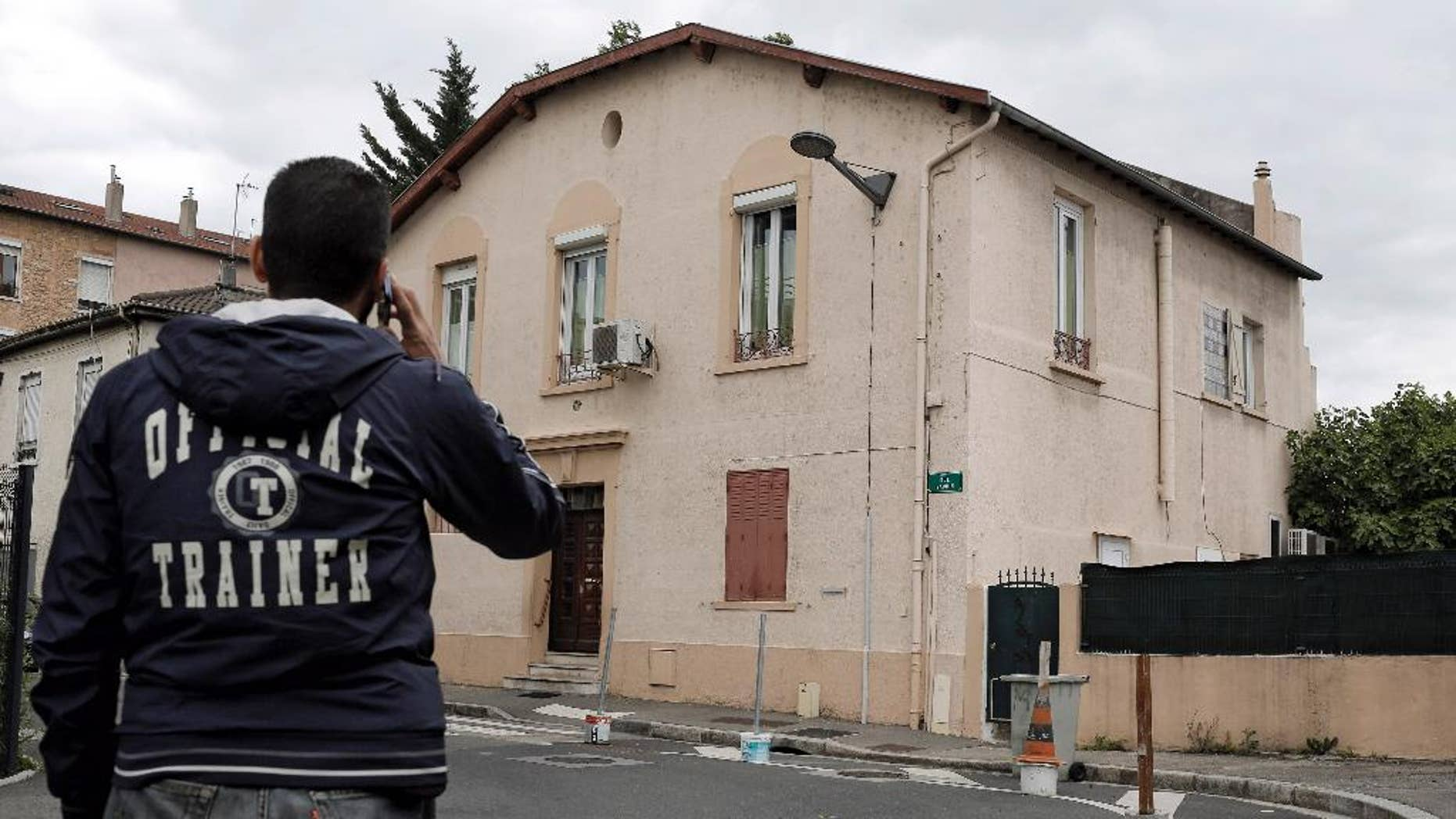 In this photo dated Tuesday, May 26, 2015 a man makes a phone call as he walk past a mosque in Oullins outside Lyon, central France. The small Oullins mosque on the edge of Lyon won an unusual court battle on Wednesday against an ultraconservative Salafist member of the congregation regarded as disruptive and, in an apparent first for Muslims, used France's 1905 law guaranteeing secularism to argue its case.(AP Photo/Laurent Cipriani)