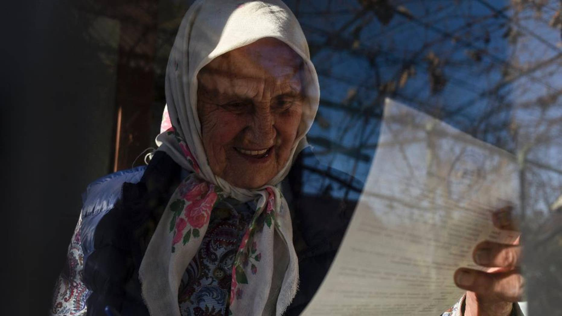 An elderly Ukrainian woman reads a ballot paper in her house during parliamentary elections in the town of Konstantinovka, Donetsk region eastern Ukraine, Sunday, Oct. 26, 2014.  Voters in Ukraine headed to the polls Sunday to elect a new parliament. (AP Photo/Evgeniy Maloletka)