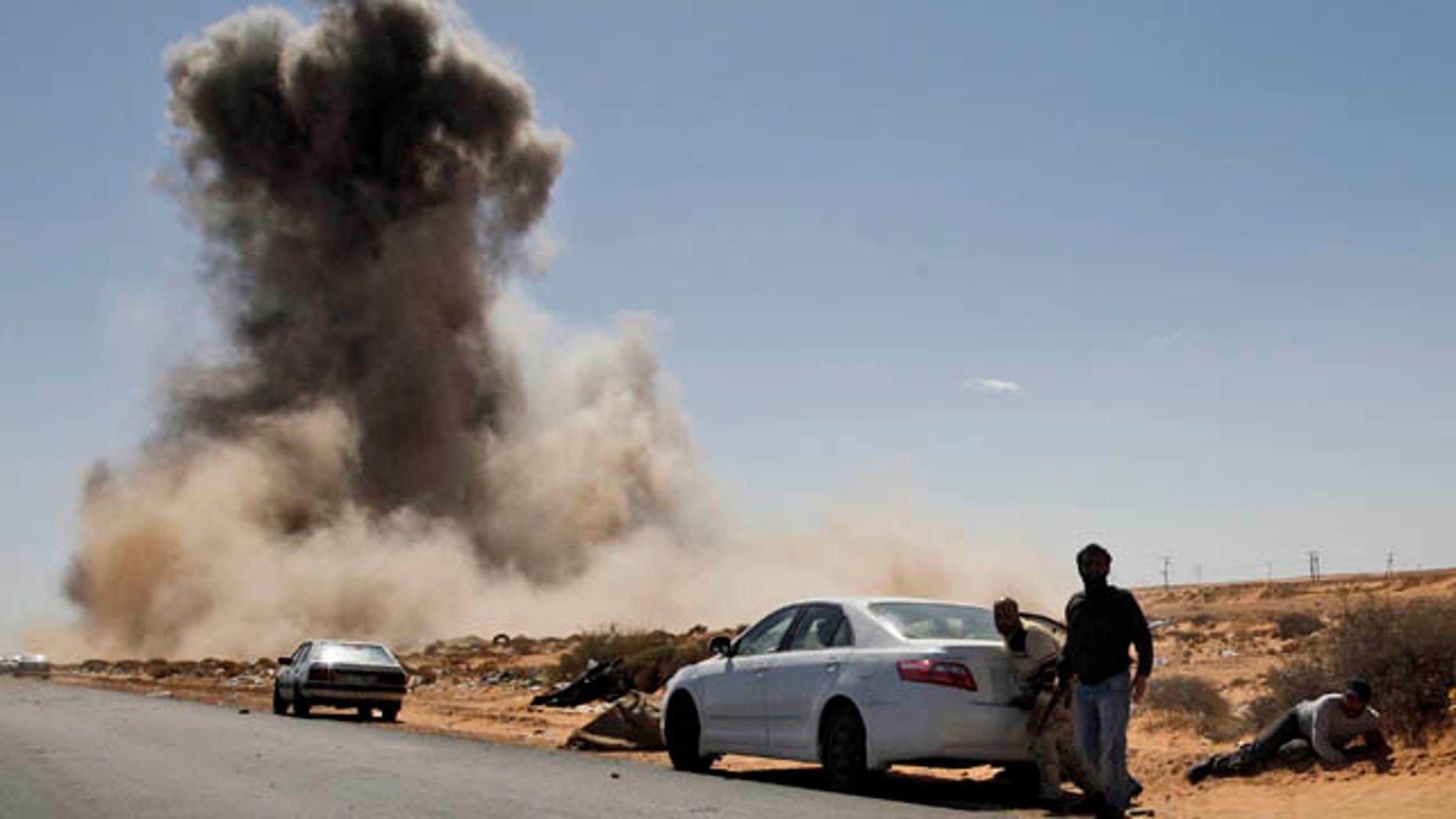 March 7: Smoke raises following an airstrike by Libyan warplanes near a checkpoint close to the anti-Libyan Leader Muammar al-Qaddafi rebels checkpoint in the oil town of Ras Lanouf, eastern Libya. (AP)