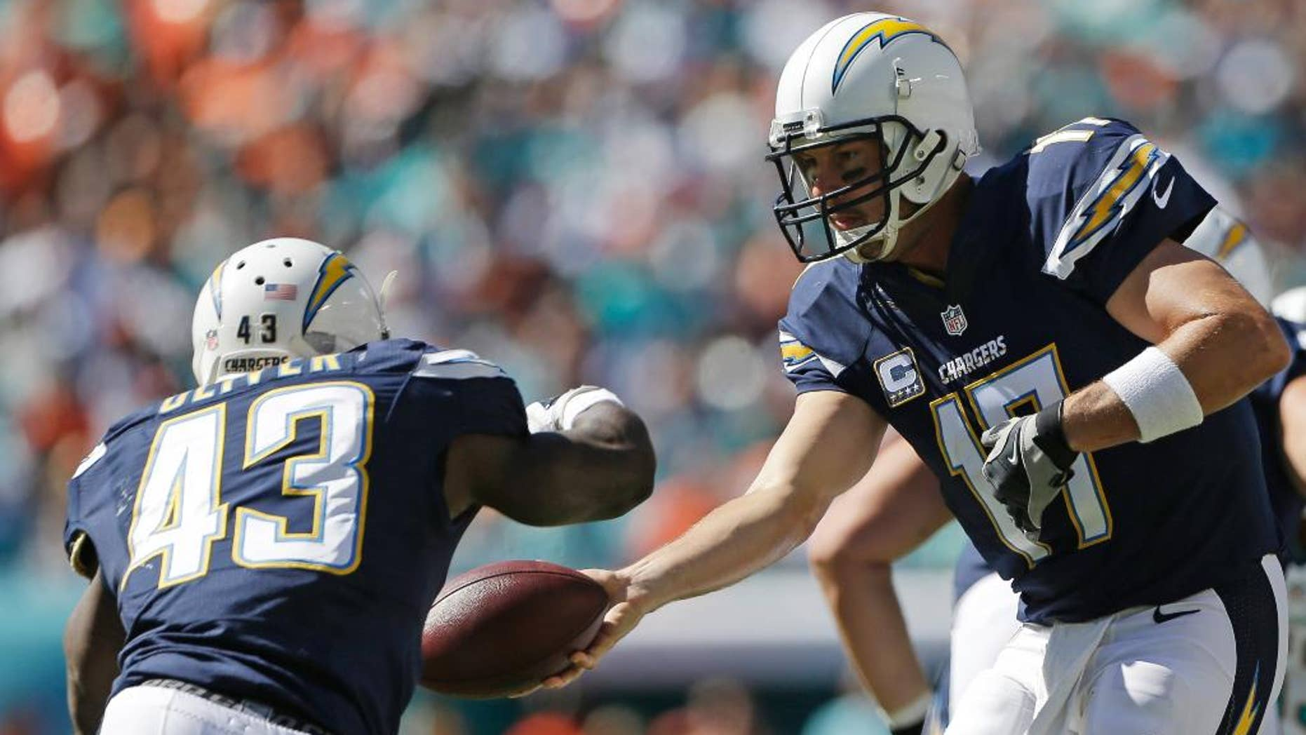San Diego Chargers quarterback Philip Rivers (17) hands the ball to running back Branden Oliver (43 ) during the first half of an NFL football game against the Miami Dolphins, Sunday, Nov. 2, 2014, in Miami Gardens, Fla. (AP Photo/Alan Diaz)