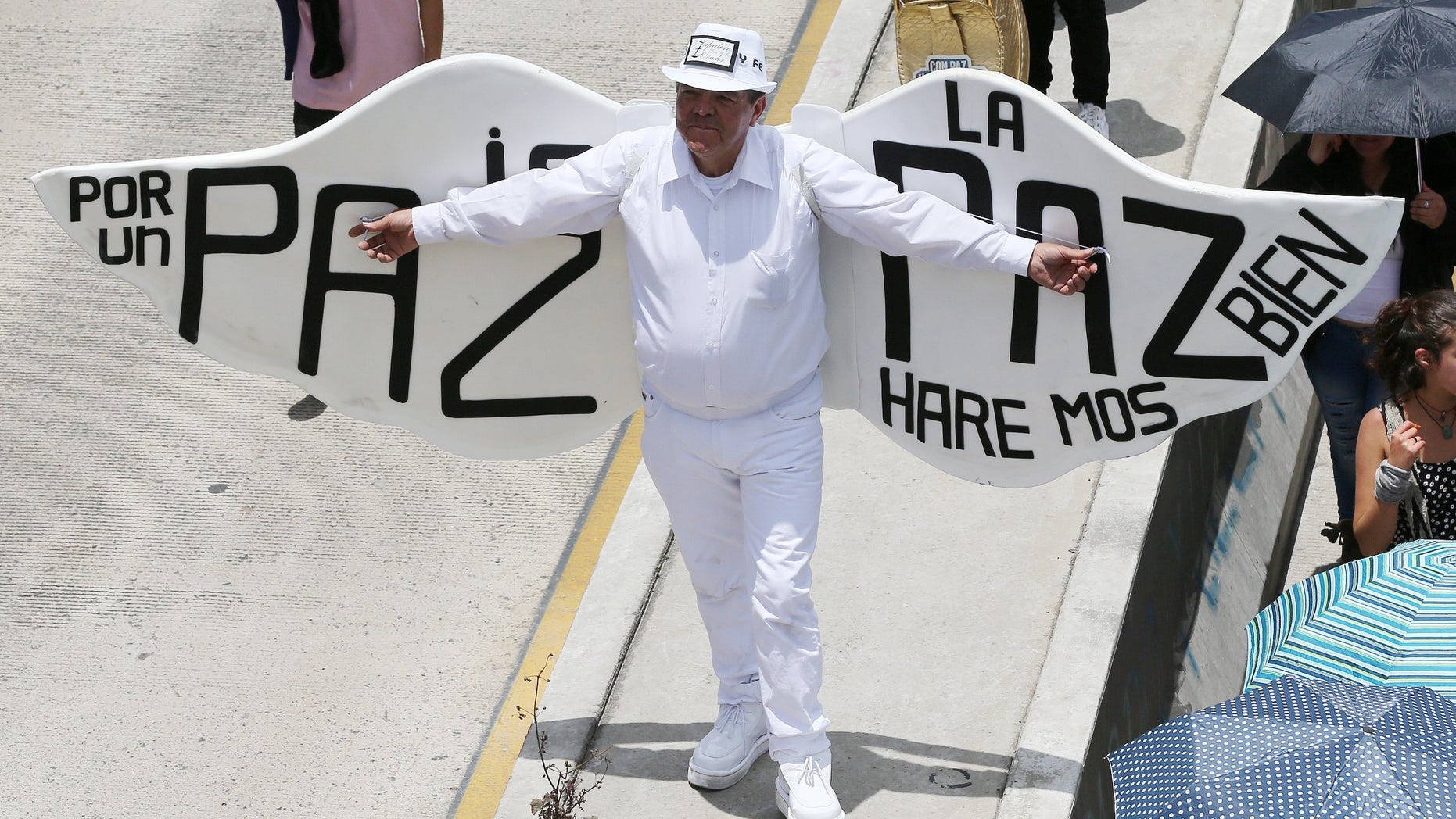 """A man, wearing angel wings, with a message that reads in Spanish; """"Peace will be good for the country,"""" takes part in a march for peace on the National Day of Memory and Solidarity with Victims of the Armed Conflict, in Bogota, Colombia, Thursday, April 9, 2015. Thousands of marchers waved white flags and paraded through cities across the country Thursday to support peace talks between the government and guerrillas, and pay tribute to victims of the nation's armed conflict. (AP Photo/Fernando Vergara)"""
