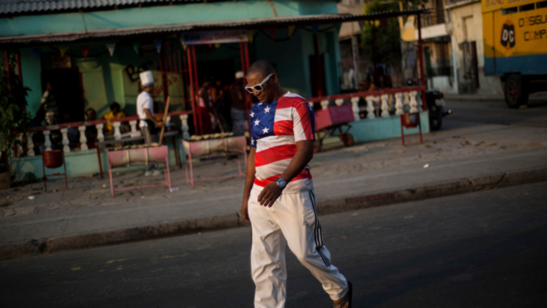 In this March 21, 2015 photo, a man wears a shirt with a U.S. flag design in Santiago, Cuba. Its easier to get from Havana to Miami than to the islands second-largest city, which has just two overbooked flights a day and trains that are achingly slow and unpredictable. (AP Photo/Ramon Espinosa)