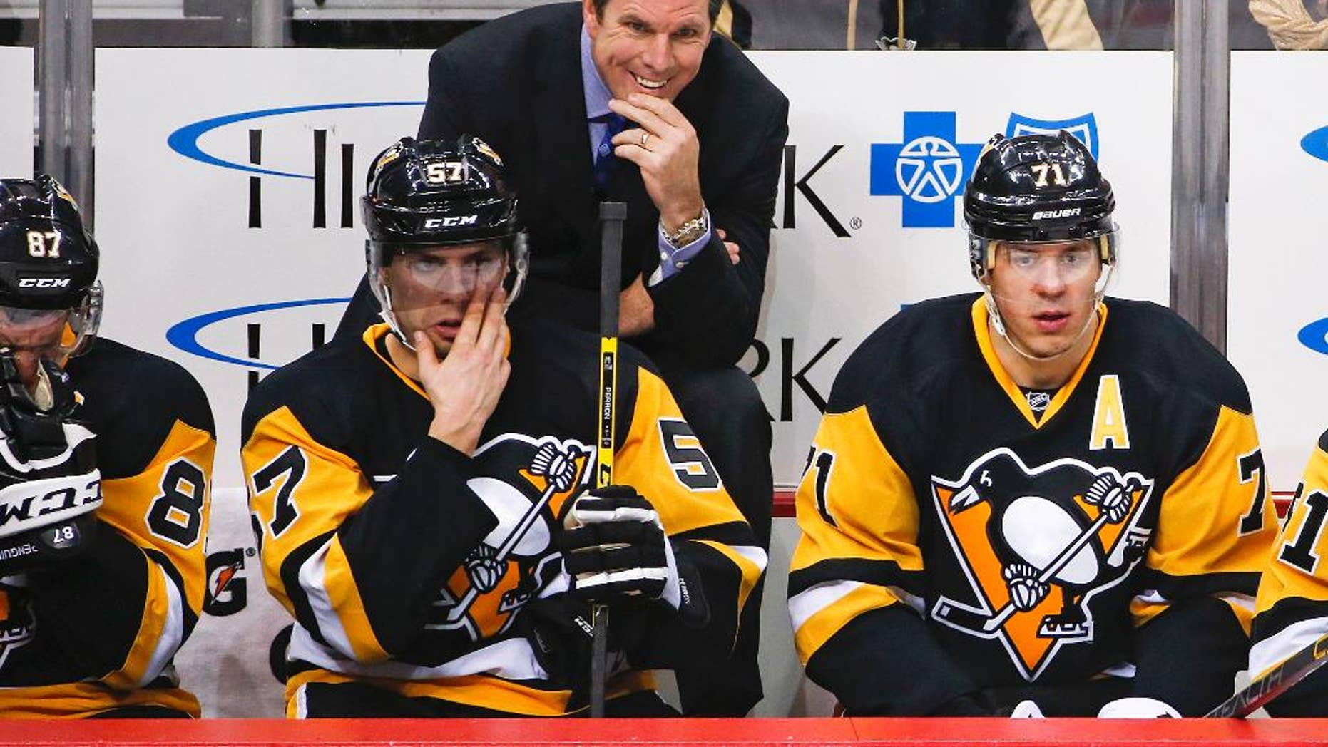 FILE - In this Jan. 2, 2016, file photo, Pittsburgh Penguins head coach Mike Sullivan stands behind David Perron (57), and Evgeni Malkin (71) during an NHL hockey game against the New York Islanders in Pittsburgh. The Penguins are on the cusp of a fourth Stanley Cup in large part to coach Sullivan's uncanny ability to get the attention of a struggling player. (AP Photo/Gene J. Puskar, File)