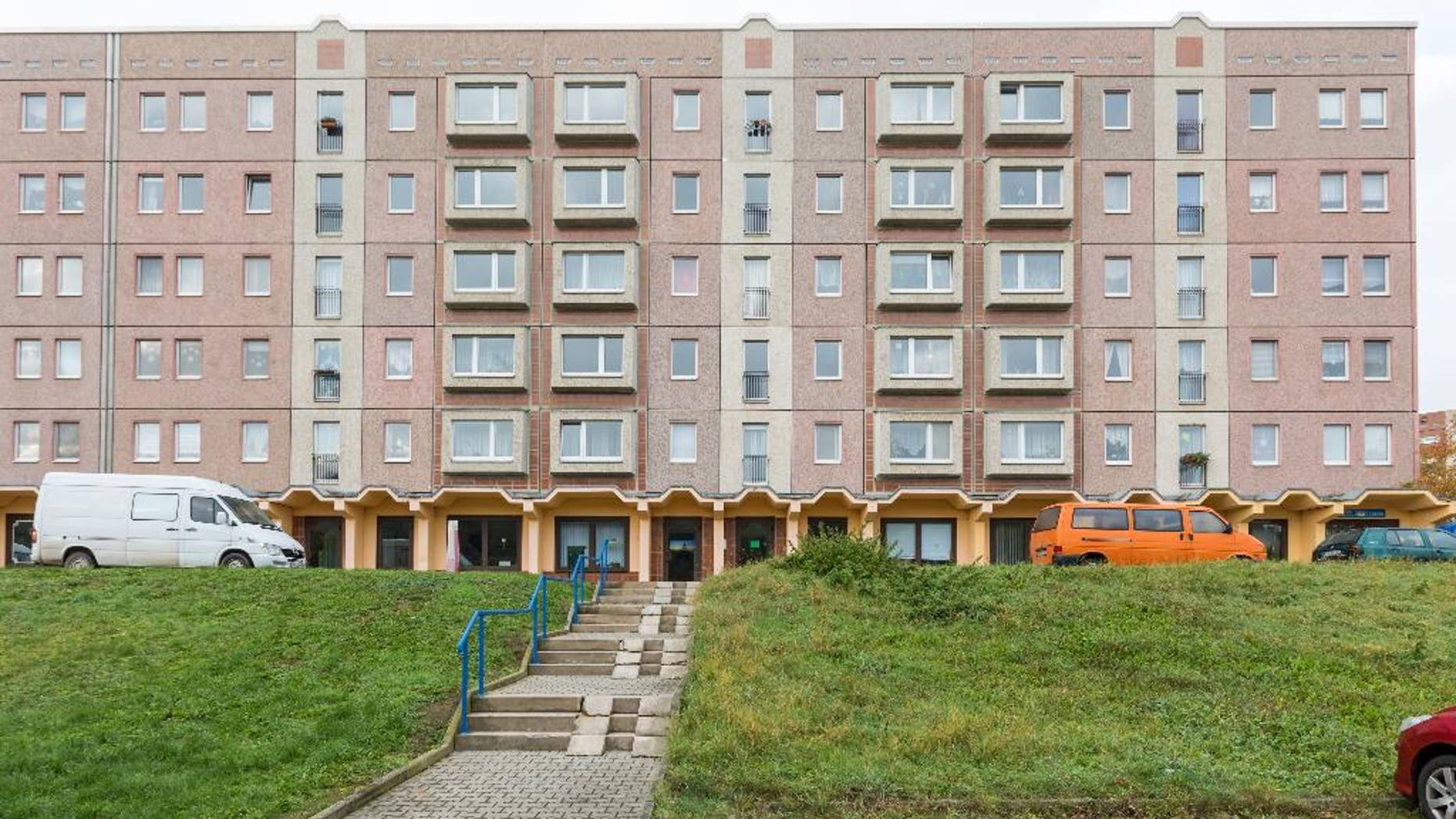 "An apartment block photographed  in Schmoelln, eastern Germany, Sunday Oct. 23, 2016.  Officers were called to this building in Schmoelln on Friday afternoon  Oct. 21, 2016 by the caregiver for a group of young migrants, who reported that a 17-year-old Somali boy was acting violently, police said. When they arrived, he was sitting on a fifth-floor window ledge. Police and fire officers tried to persuade the teenager not to jump, but he leapt and died shortly afterward of his injuries.   Onlookers apparently shouted ""Jump!"" before the  teenage migrant leapt from the  apartment block in the  eastern German town, suffering fatal injuries, the mayor said Saturday Oct. 22, 2016 .  (Michael Reichel/dpa via AP)"
