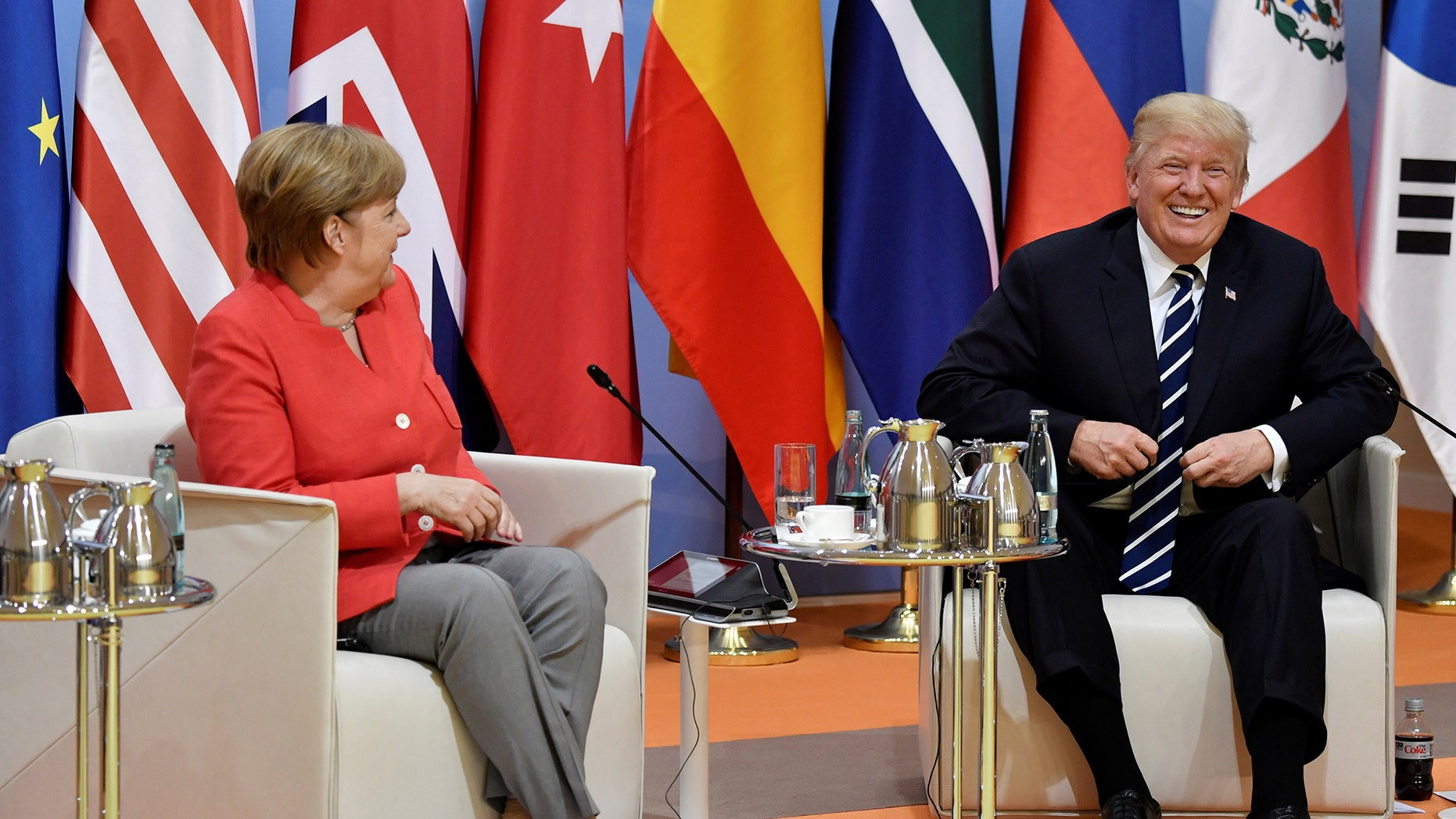 """German Chancellor Angela Merkel and US President Donald Trump share a laugh at the start of the """"retreat meeting"""" on the first day of the G20 summit in Hamburg, Germany, July 7, 2017. REUTERS/John MACDOUGALL,POOL - RTX3AG9G"""