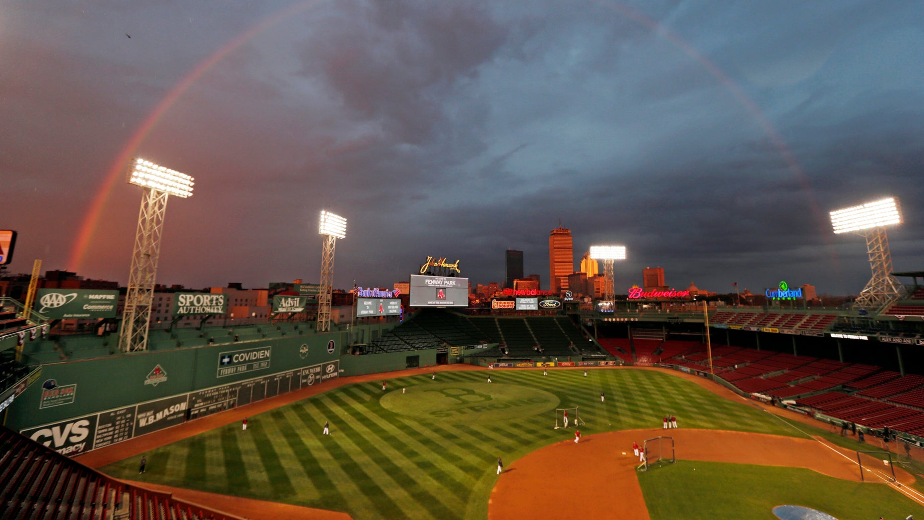 Boston Red Sox players take batting practice as a rainbow appears in the sky above Fenway Park Tuesday, Oct. 22, 2013, in Boston. The Red Sox are scheduled to host the St. Louis Cardinals in Game 1 of baseball's World Series on Wednesday.  (AP Photo/Charles Krupa)