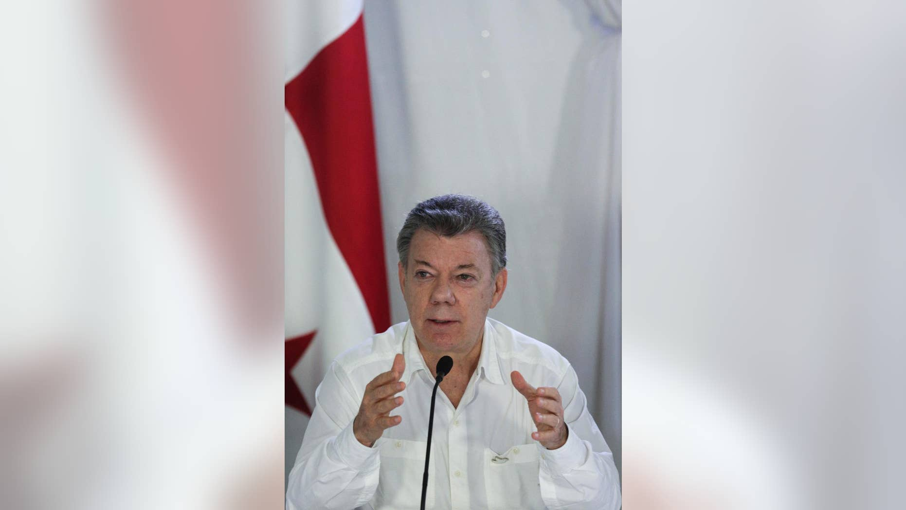 Colombia's President Juan Manuel Santos speaks during a press conference after a meeting with his Panamanian counterpart Juan Carlos Varela at the Nicanor Air Naval base in Darien province, Panama, Tuesday, Oct. 25, 2016. Santos and Varela discussed security and immigration issues between both countries. (AP Photo/Arnulfo Franco)