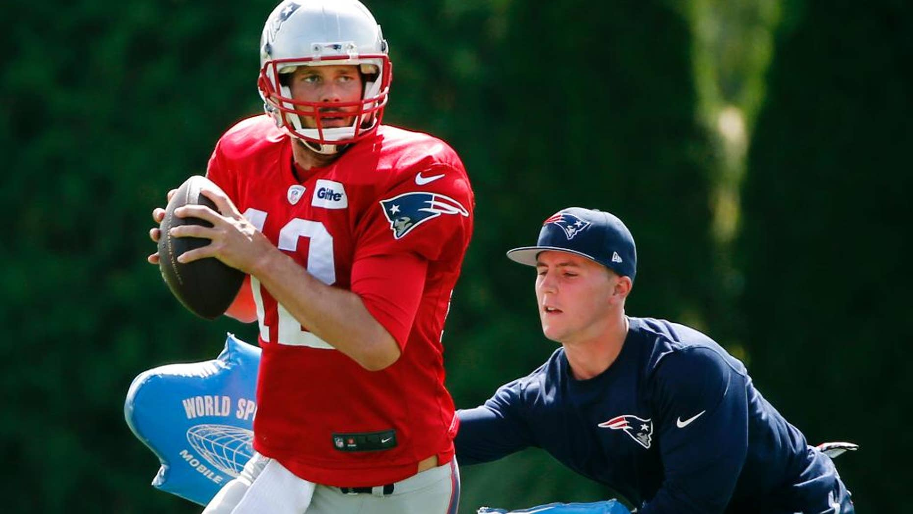 New England Patriots quarterback Tom Brady passes under pressure during a drill at team practice in Foxborough, Mass., Wednesday, Sept. 3, 2014. The Patriots are preparing for their opening NFL football game against the Miami Dolphins on Sunday in Miami. (AP Photo/Elise Amendola)