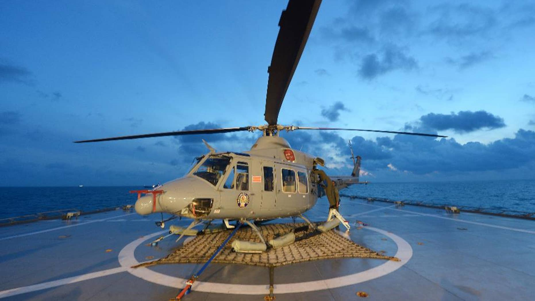 Indonesian navy personnel check a helicopter as they prepare operations to lift the tail of AirAsia Flight 8501 in Java sea, Indonesia Friday, Jan. 9, 2015. Days after sonar detected apparent wreckage, an unmanned underwater vehicle showed the plane's tail, lying upside down and partially buried in the ocean floor. (AP Photo/Adek Berry, Pool)