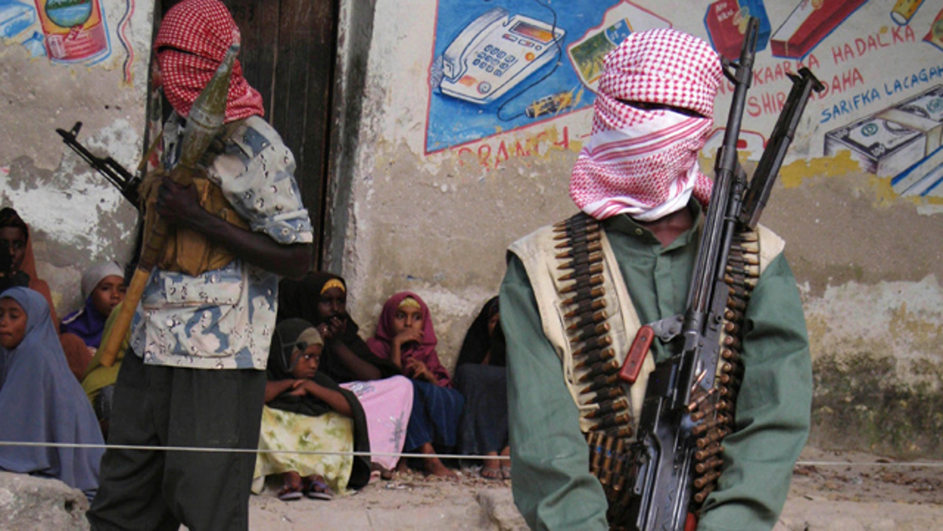 Dec. 18, 2008: Somali al-Shabaab fighters stand stand guard during a public flogging by the hardline Islamic group in Bula Marer town.
