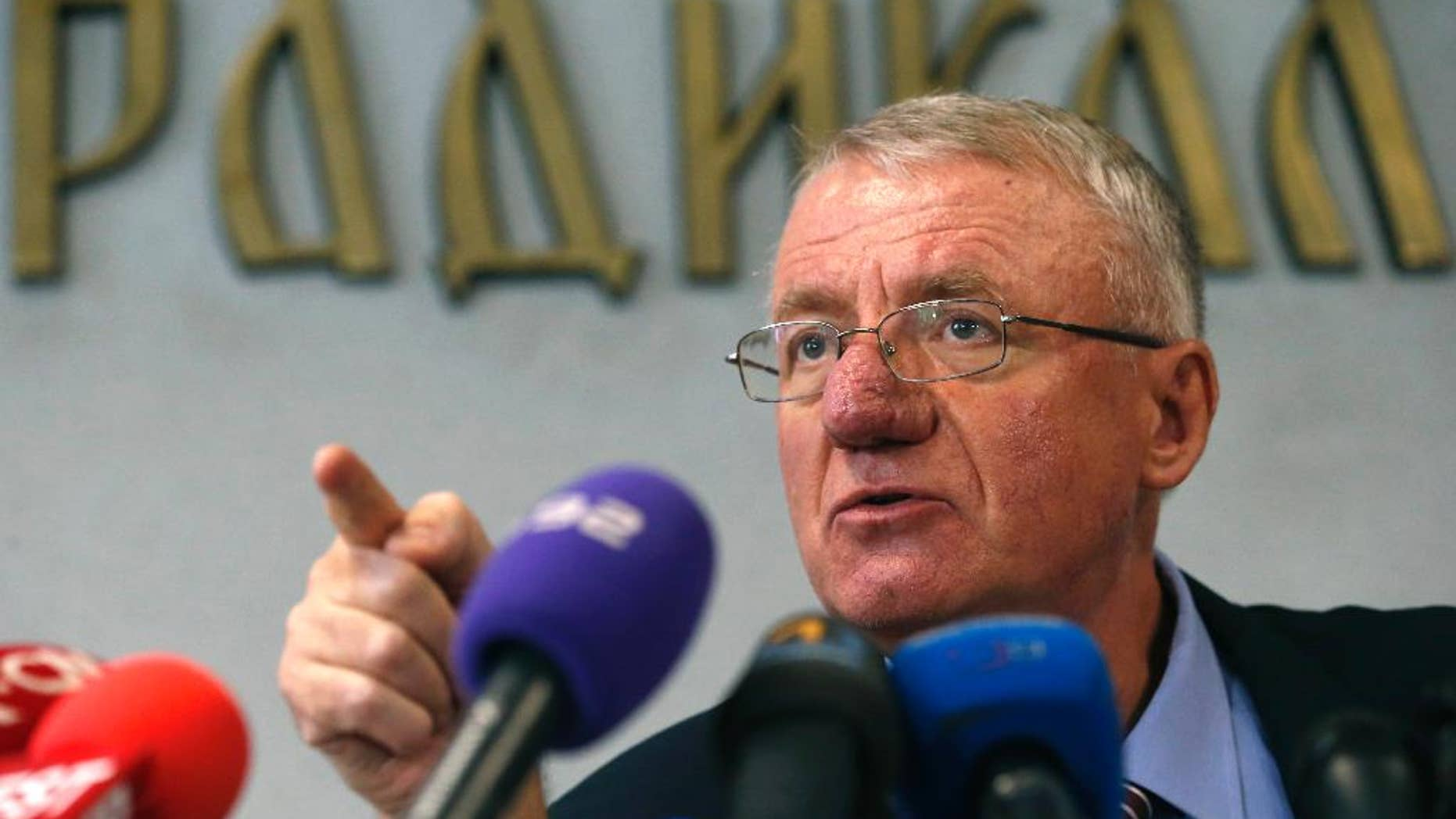 FILE - This is a Thursday, Nov. 13, 2014  file photo of Serbian far-right leader Vojislav Seselj as he speaks during a press conference in Belgrade, Serbia.  Appeals judges at the Yugoslav war crimes tribunal ruled Monday March 30, 2015 that Serbian far-right leader Vojislav Seselj has breached conditions of his provisional release and must return to the court's cellblock in The Hague. (AP Photo/Darko Vojinovic, File)