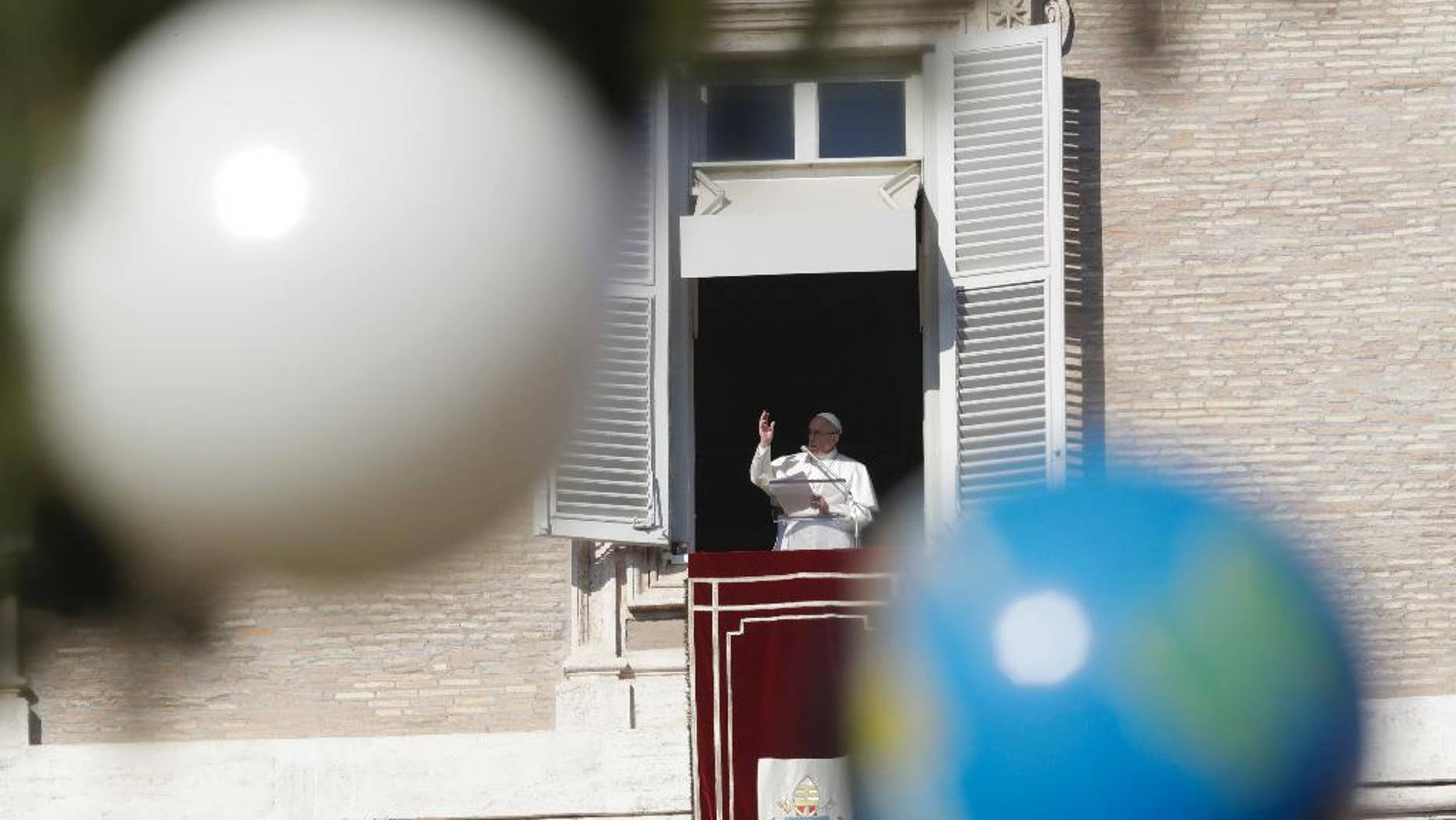 Pope Francis is framed by Christmas tree decorations during the Angelus prayer from the window of his studio overlooking St Peter square at the Vatican, Sunday, Jan. 1, 2017.(AP Photo/Andrew Medichini)