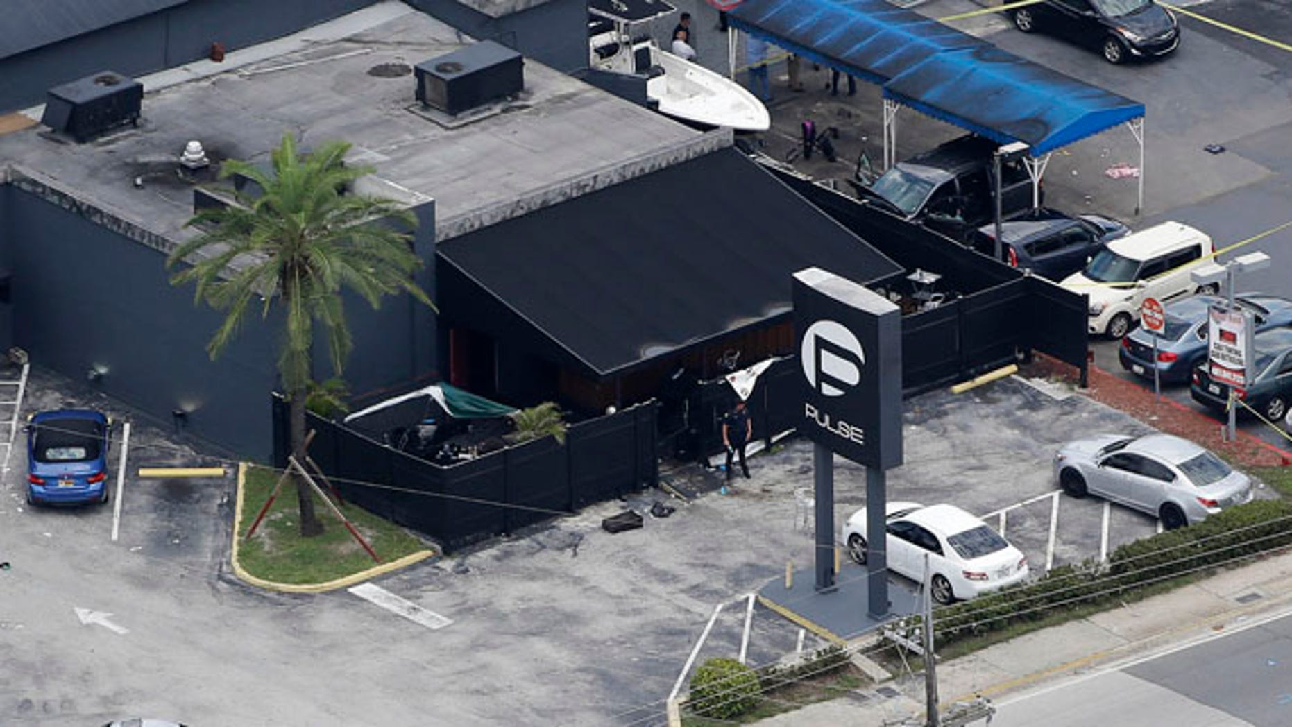 Law enforcement officials work at the Pulse gay nightclub in Orlando, Fla.