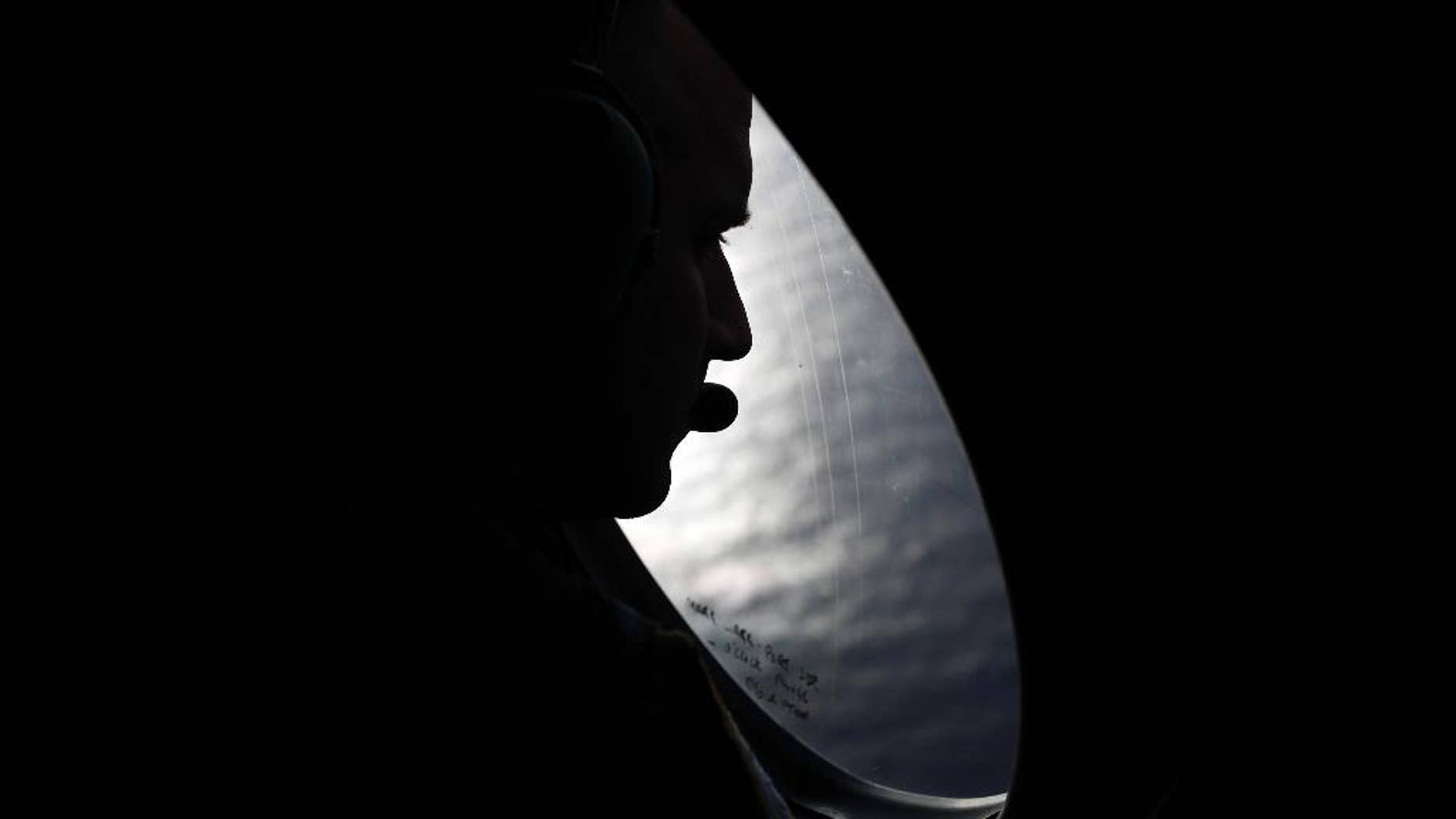 A Royal New Zealand Air Force crew member looks into the southern Indian Ocean from a P-3K2 Orion aircraft searches for missing Malaysian Airlines flight 370, Saturday, March 29, 2014. A day after the search for the Malaysian jetliner shifted to a new area of the Indian Ocean, ships on Saturday plucked objects from the sea to determine whether they were related to the missing jet. None were confirmed to be from the plane, leaving searchers with no sign of the jet three weeks after it disappeared. (AP Photo/Jason Reed, Pool)