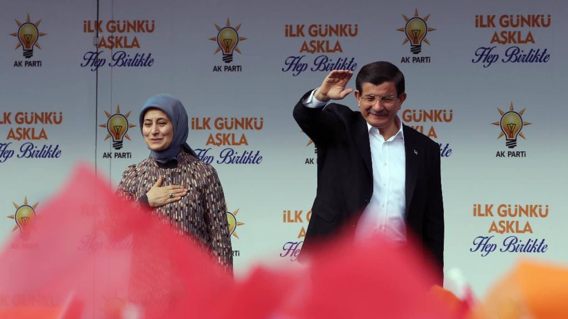Turkish Prime Minister Ahmet Davutoglu and his wife Sare Davutoglu salute cheering supporters during a rally in Ankara, Turkey, Saturday, Oct. 31, 2015. (AP Photo/Burhan Ozbilici)