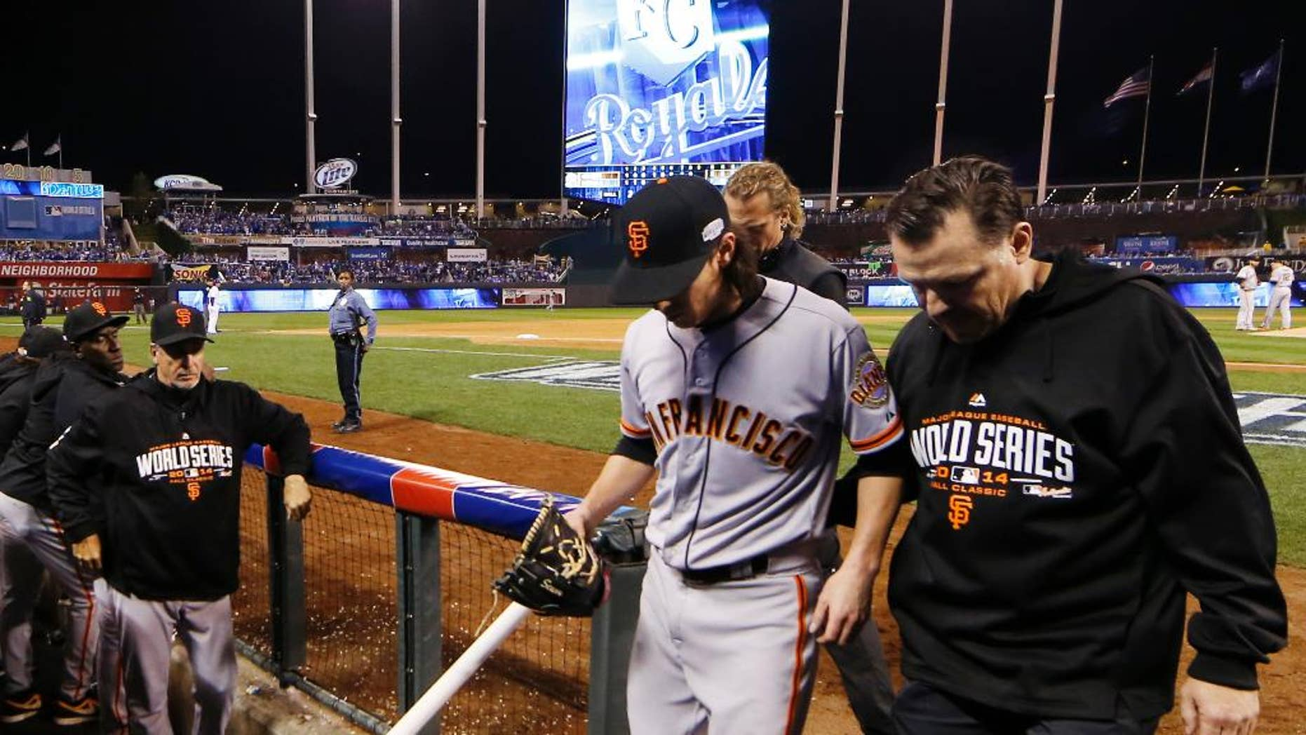 San Francisco Giants pitcher Tim Lincecum is helped into the team's dugout during the eighth inning of Game 2 of baseball's World Series Wednesday, Oct. 22, 2014, in Kansas City, Mo. Kansas City Royals defeated the Giants 7-2 to tie the series at 1-1 games. (AP Photo/Matt Slocum)