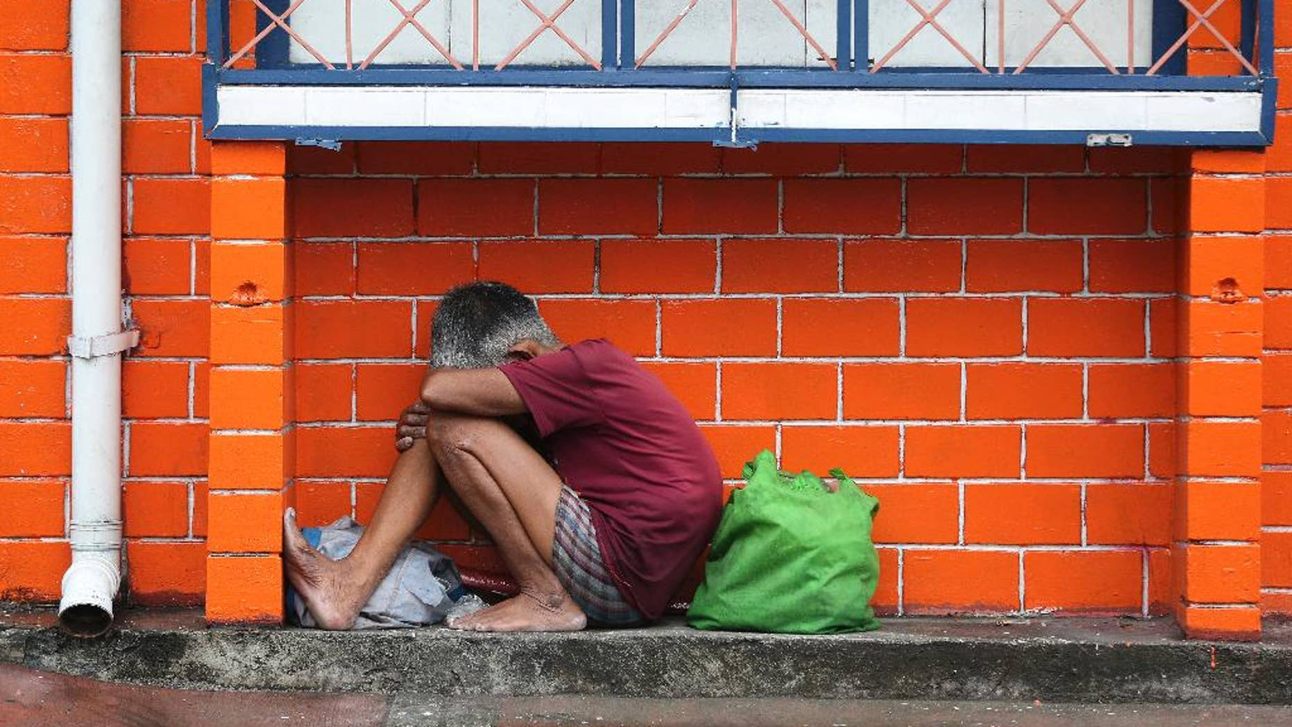 A Filipino woman takes shelter from rain caused by Typhoon Melor as the lowest level storm signal warning has been raised in Manila, Philippines Tuesday, Dec. 15, 2015. Typhoon Melor weakened Tuesday as it crossed over the central Philippines, leaving one man dead and wide areas without power. (AP Photo/Aaron Favila)