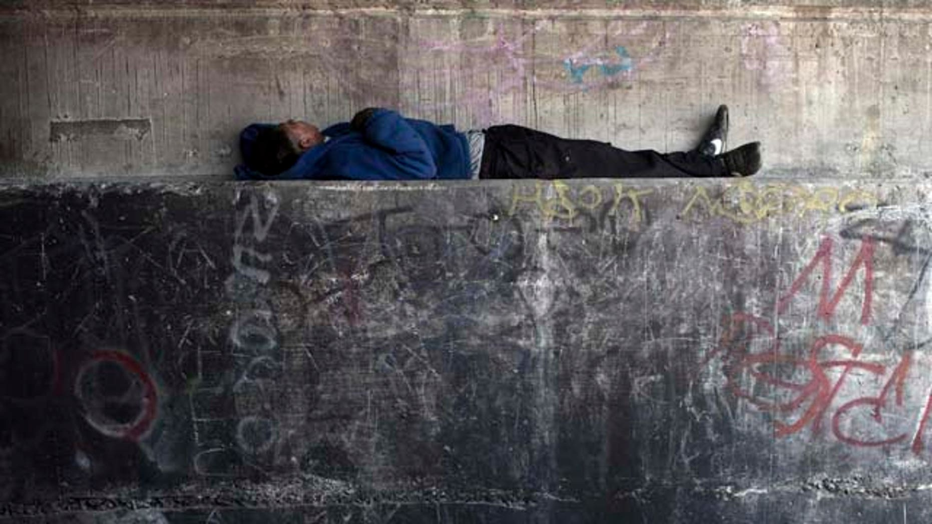 In this photo taken June 22, 2011, a homeless men tries to rest inside a Tijuana River canal, in Tijuana, Mexico. During the day, deportees who find themselves in Tijuana look for work and flee Mexican police, who will jail them for not having papers, just like in the U.S. At night they take refuge in the canals, beneath bridges or in shacks, among drug addicts and people with mental health problems; a few feet from the rusty barrier that separates the country of their birth from the country where they worked years for a better life.  (AP Photo/Alejandro Cossio)