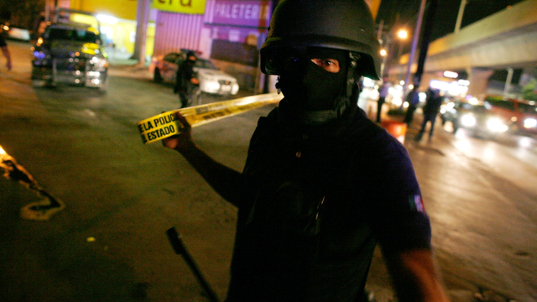 A policeman cordons off a crime scene where gunmen tried to kidnapp a government official outside the Topo Chico prison in Monterrey, June 11, 2010. A rift between drug gangs near the U.S. border is terrifying Mexico's richest city Monterrey, once a poster child of development, forcing a quarter of its export factories to freeze investment. A gruesome war between Mexico's powerful Gulf cartel and its former armed wing, the Zetas, has killed a record 290 people in Monterrey and surrounding areas since the start of the year, when the two groups split and bloodshed escalated. Picture taken June 11, 2010. REUTERS/Tomas Bravo (MEXICO - Tags: CIVIL UNREST CRIME LAW POLITICS SOCIETY)