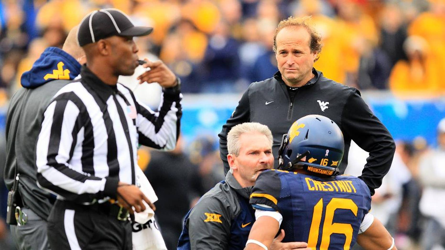 West Virginia coach Dana Holgorsen looks on as Terrell Chestnut (16) is looked over by the medical staff during the second half of an NCAA college football game against Baylor in Morgantown, W.Va., Saturday, Oct. 18, 2014. West Virginia won 41-27. Chestnut left the game with a concussion. (AP Photo/Chris Jackson)