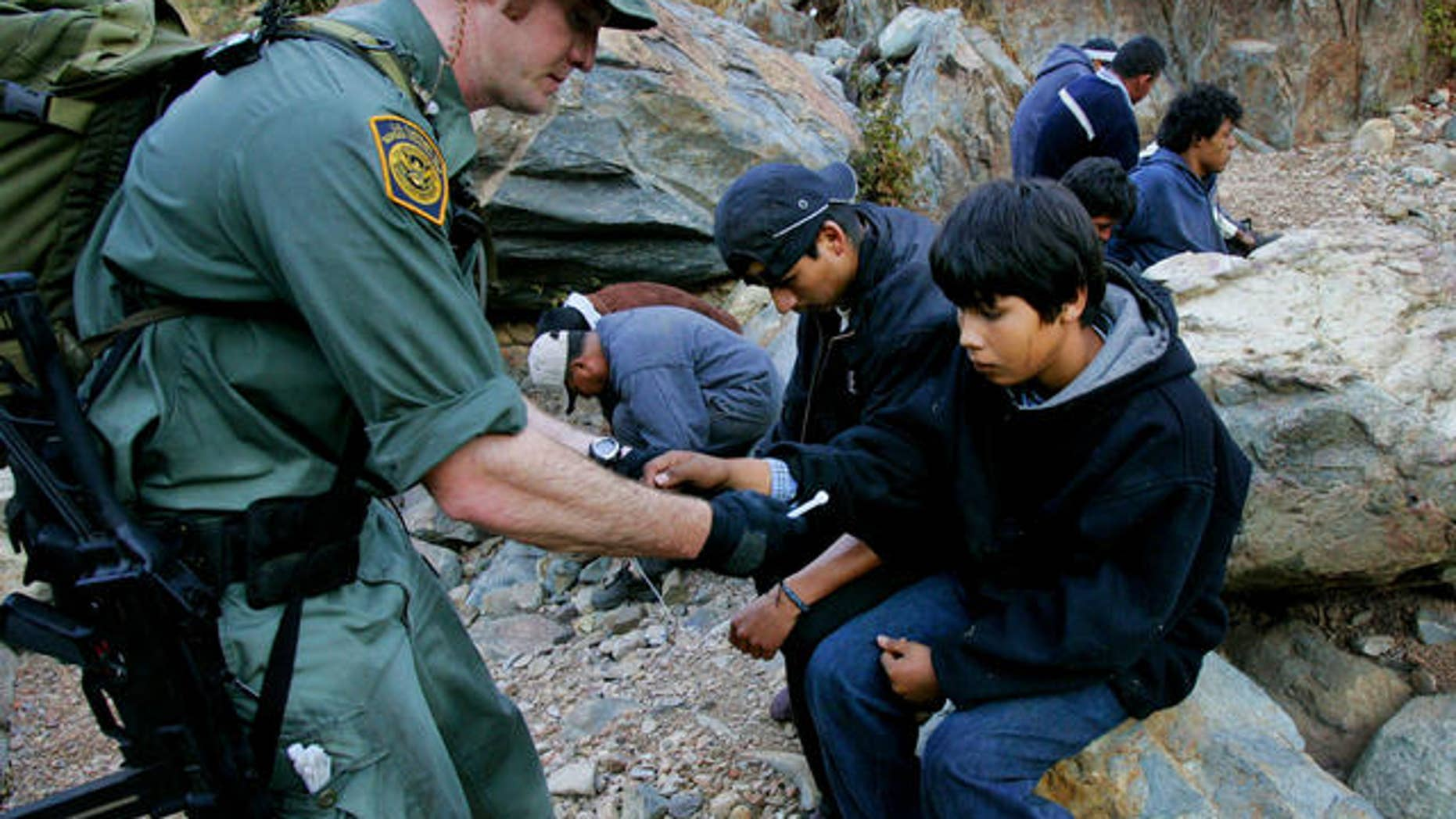 Border patrol agent Jeff Mielke secures plastic handcuffs on a group of undocumented immigrants caught in the Otay Mesa Mountain Range, just east of San Diego.