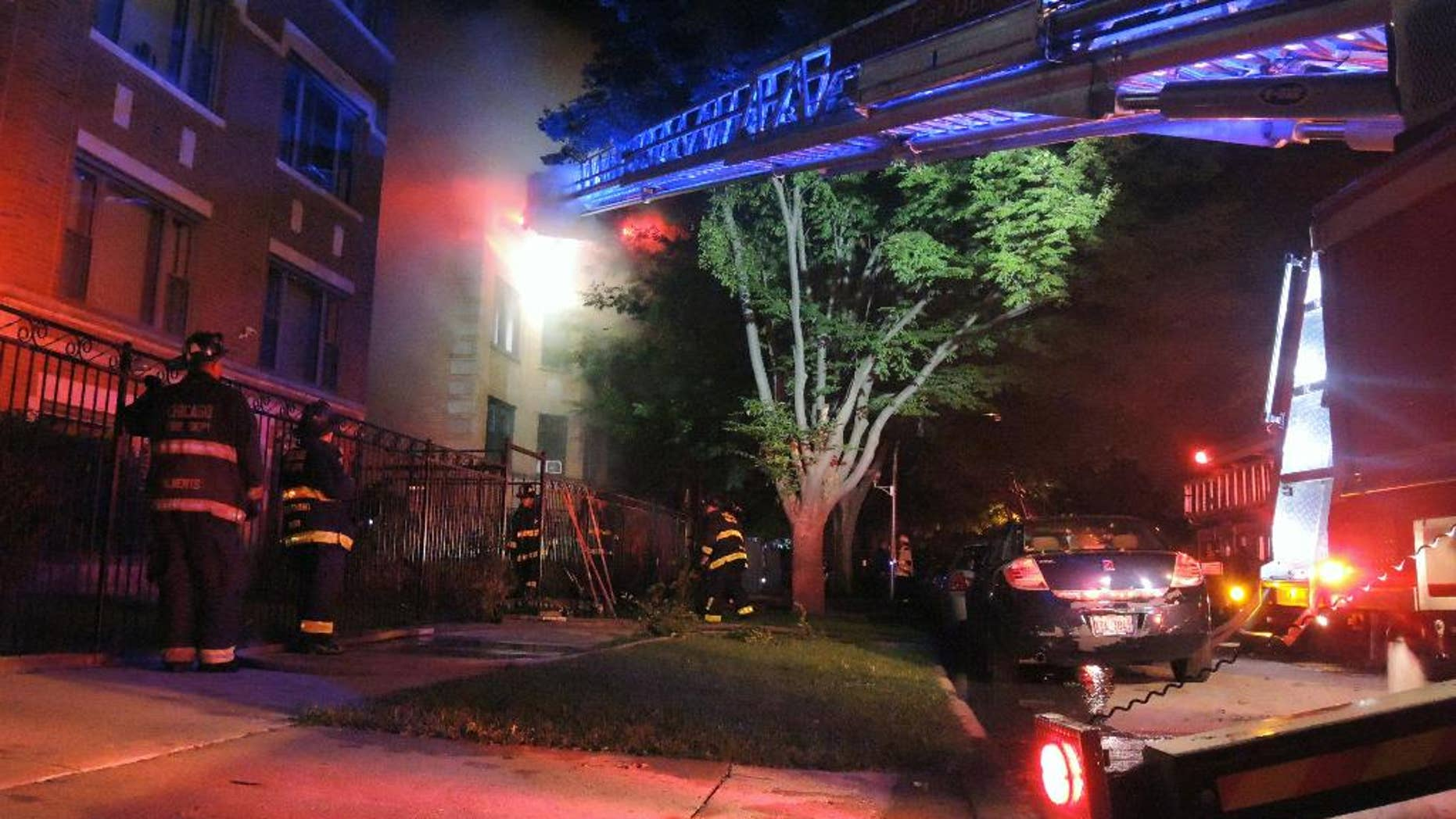 Chicago firefighters battle an apartment fire in the 8100 block of South Essex Avenue in the South Chicago neighborhood early on Tuesday, Aug. 23, 2016. The fire at a Chicago apartment building that appears to have been deliberately set killed multiple people Tuesday, police said. (Alexandra Chachkevitch/Chicago Tribune via AP)