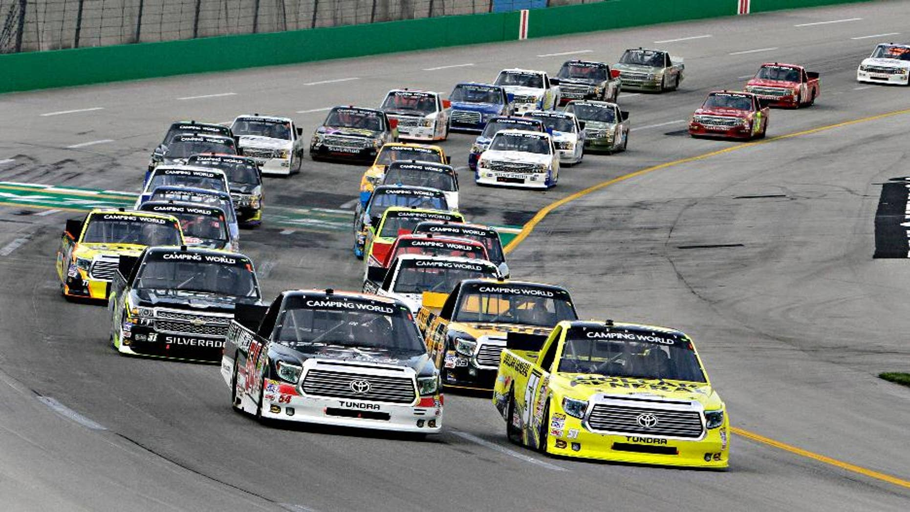 Pole-sitter Kyle Busch, right, leads the field into the first lap of the NASCAR Trucks auto race at Kentucky Speedway in Sparta, Ky., Thursday June 26, 2014. Darrell Wallace Jr. is at front left. (AP Photo/Garry Jones)