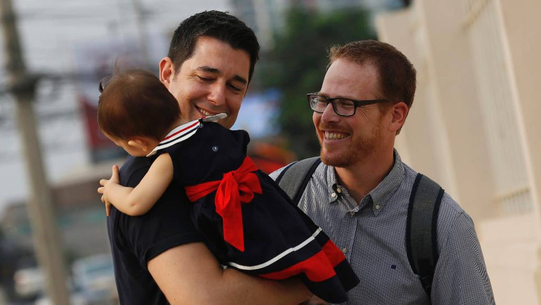 Manuel Santos, left, and Gordon Lake with their baby, Carmen, in March.