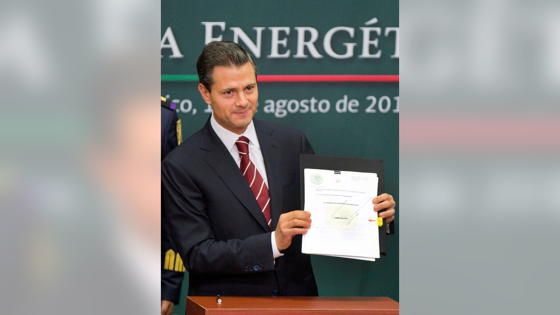 FILE - In this Aug. 12, 2013 file photo, Mexico's President Enrique Pena Nieto shows to the audience his proposal that would allow private firms to participate in the oil industry in Mexico City. The opening of Mexico's oil industry to private and foreign investment caps a remarkable series of legislative victories by President Pena Nieto, who istrying to re-engineer the country's most dysfunctional institutions. (AP Photo/Eduardo Verdugo, File)