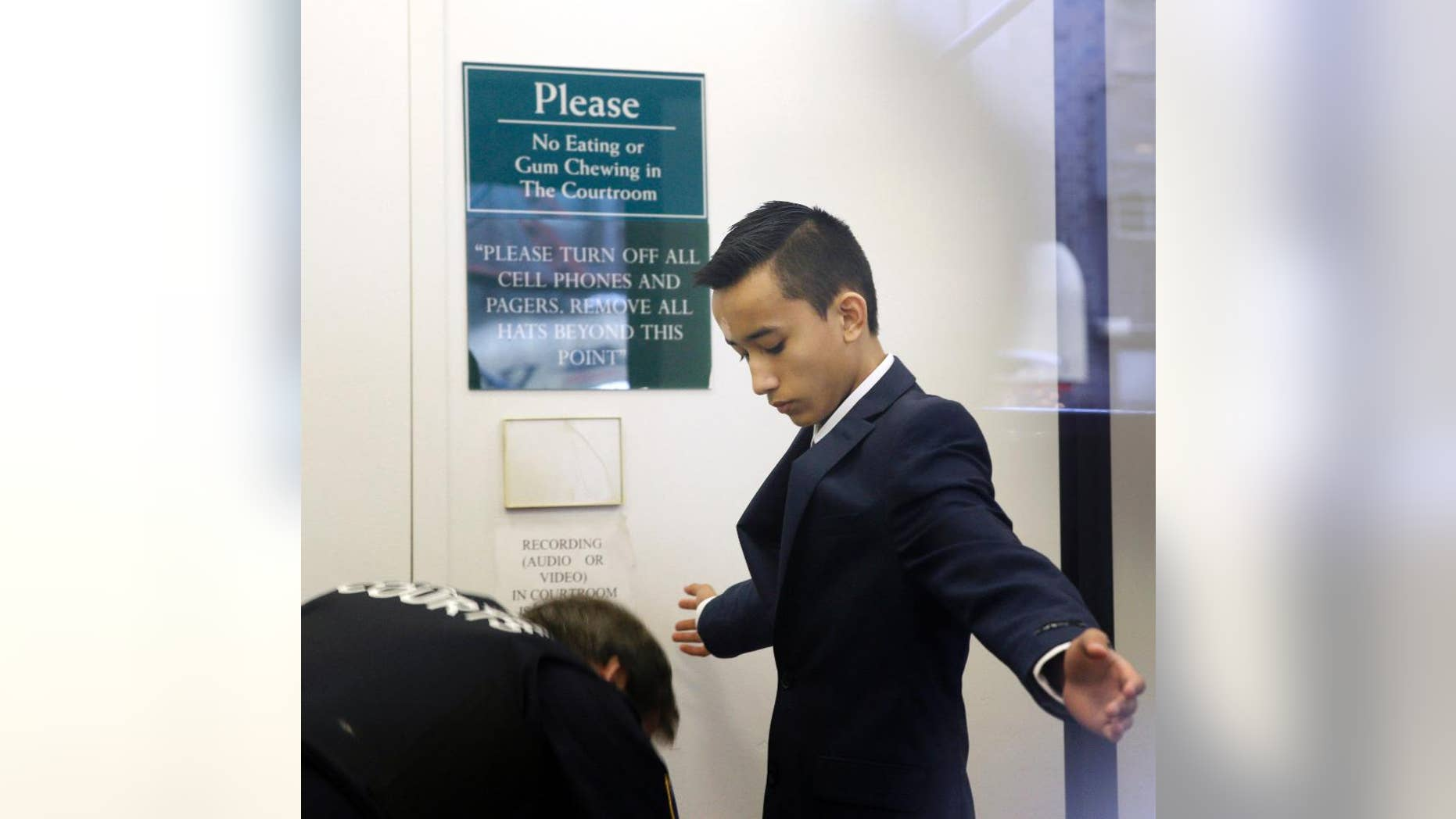FILE- In this April 2, 2014 file photo, Justin Casquejo passes through security at a courthouse in New York. The teenage daredevil who climbed the World Trade Center's centerpiece tower in 2014 has surrendered to police on Friday, Dec. 2, 2016, after videos posted on social media showed him dangling from other Manhattan skyscrapers. (AP Photo/Seth Wenig, File)