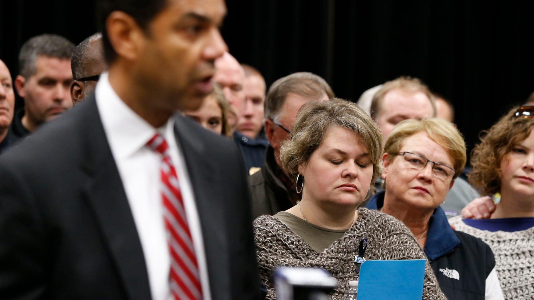 Beth Stauffer, center, reacts on Sunday, Dec. 29, 2013,  as FBI Special Agent in Charge Danile McMullen announces they believe the bank robber who killed her husband, Sgt. Gale Stuaffer on Monday, was killed attempting another bank robbery in Phoniex, Ariz., on Saturday in Tupelo, Miss. (AP Photo/Northeast Mississippi Daily Journal, Thomas Wells) MANDATORY CREDIT