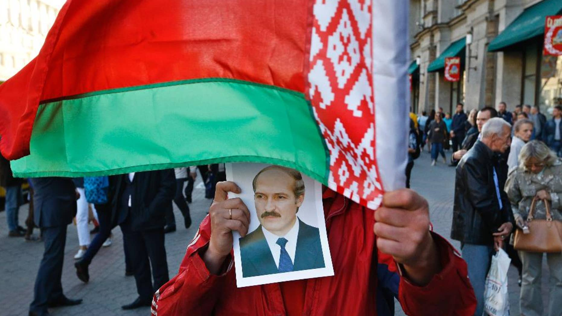 A supporter of Belarusian President Alexander Lukashenko holds his portrait and waves a state flag in downtown Minsk, Belarus, Thursday, Sept. 10, 2015. Presidential elections in Belarus are scheduled for October 11, 2015. (AP Photo/Sergei Grits)