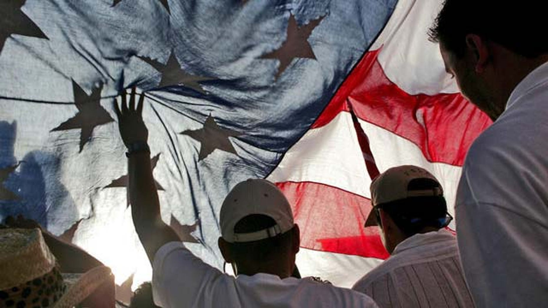 Immigration rights demonstrators hold a U.S. flag aloft during a march along Wilshire Boulevard, Monday, May 1, 2006, in Los Angeles. (AP Photo/Stefano Paltera)