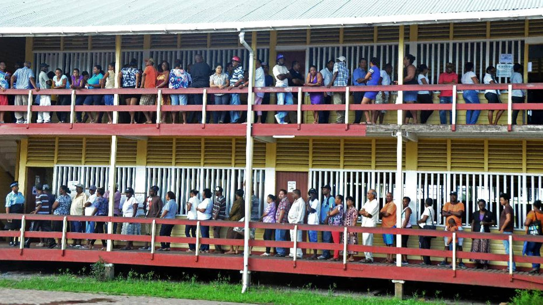 Voters line up to cast their votes at the FE Pollard Primary School in Georgetown, Guyana, Monday, May 11, 2015. A party in power for over two decades in Guyana faced off in general elections Monday against a new coalition of opposition parties that seeks to challenge a tradition of racial politics and accuses the government of mismanagement and corruption. (AP Photo/Adrian Narine)