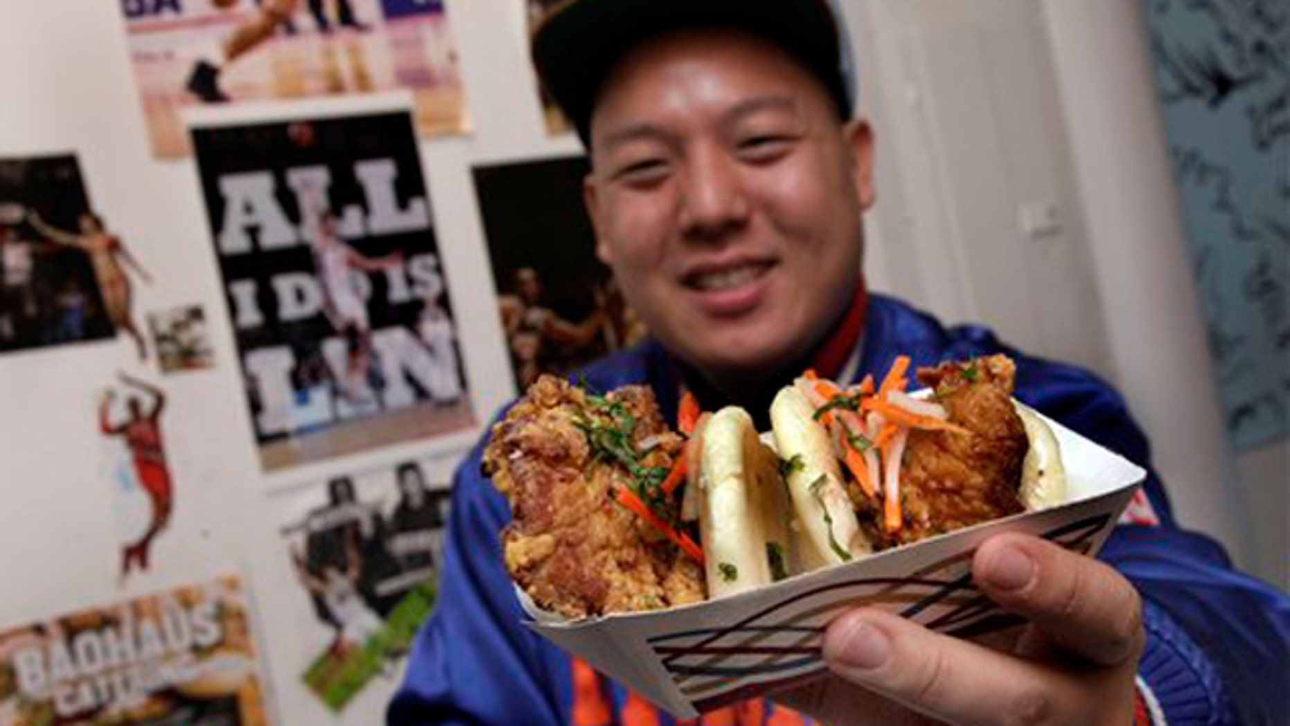 """Feb. 17, 2012: Eddie Huang, co-owner of Baohaus, holds a pair of  """"The Taiwanese Te-Bao,"""" a Taiwanese pork chop with curry seasoning, pickles daikon-carrot, jalapeno, aioli and cilantro in a steamed bun, in the New York restaurant."""