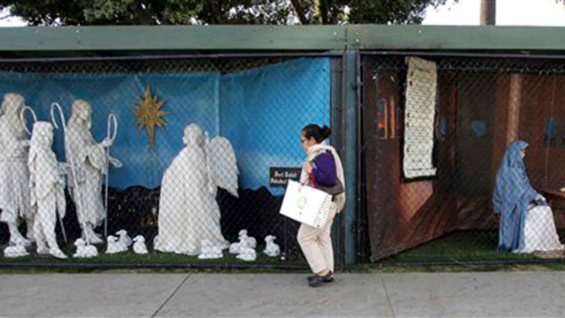 FILE - In this Dec. 13, 2011 file photo, a woman walks past a two of the traditional displays showing the Nativity scene along Ocean Avenue at Palisades Park in Santa Monica, Calif.