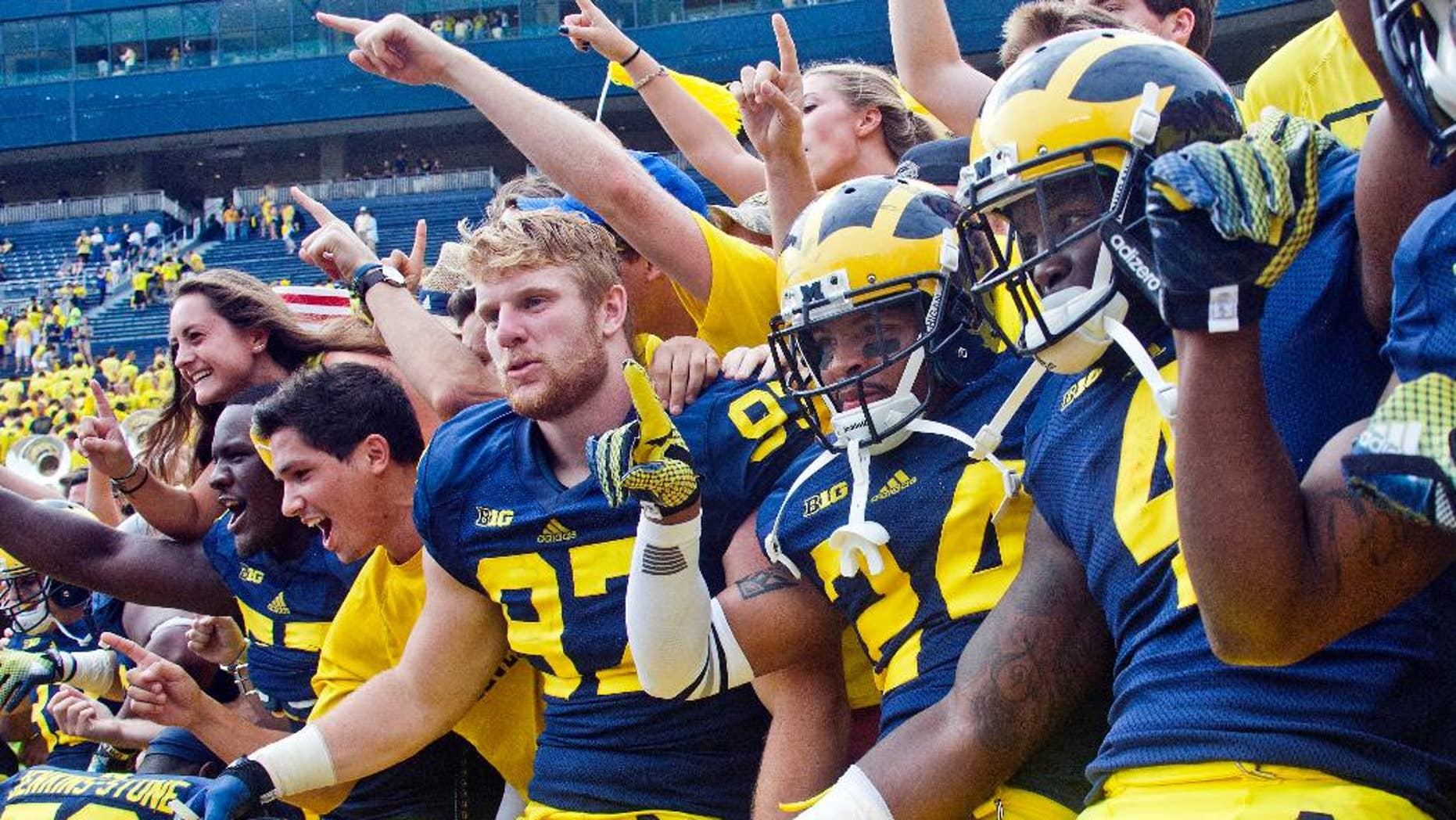 Michigan defensive end Brennen Beyer (97), defensive back Delonte Hollowell (24), and running back De'Veon Smith (4) celebrate in the stands with student fans after beating Appalachian State 52-14 in an NCAA college football game in Ann Arbor, Mich., Saturday, Aug. 30, 2014. (AP Photo/Tony Ding)