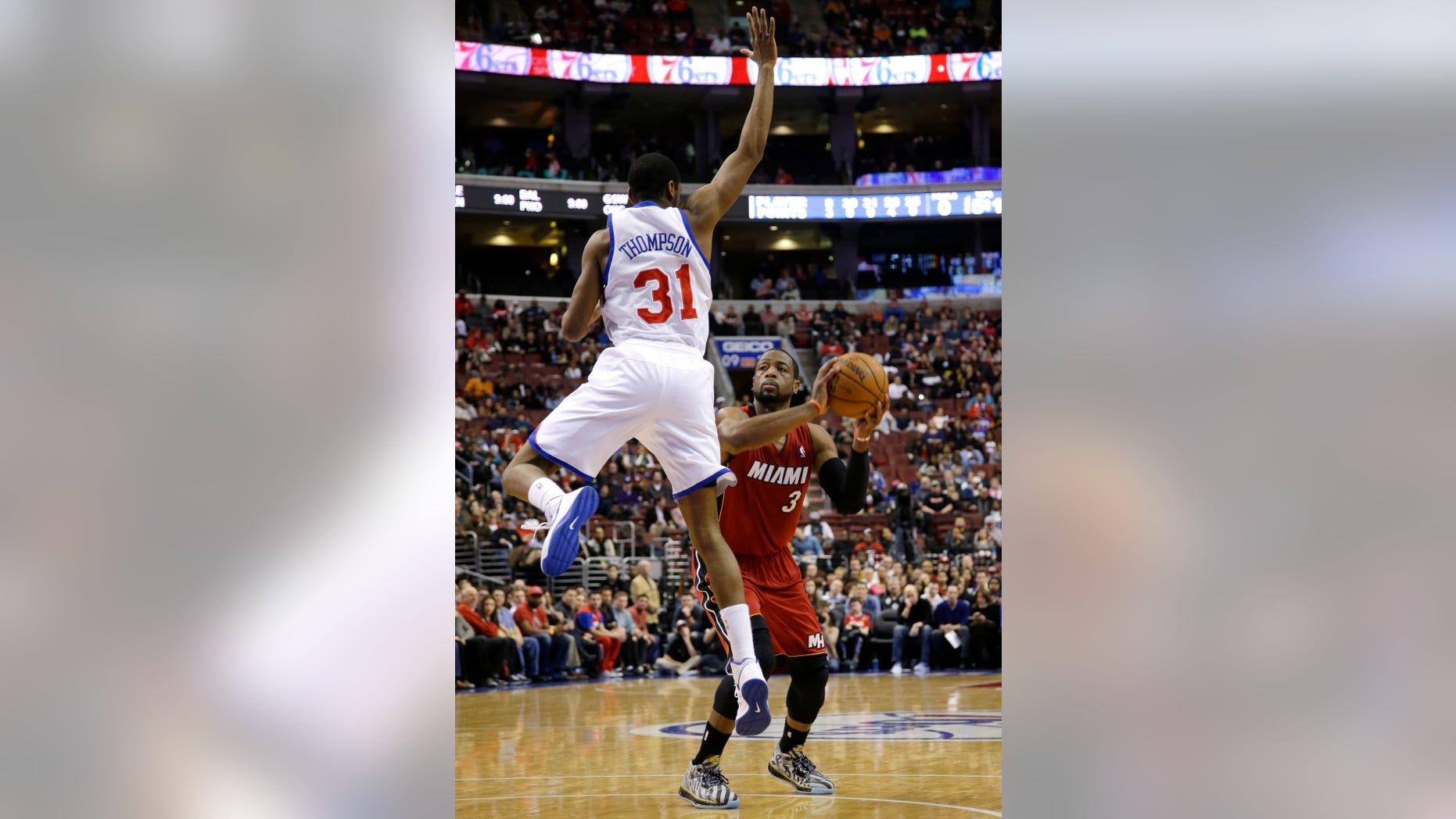 Miami Heat's Dwyane Wade (3) prepares to shoot against Philadelphia 76ers' Hollis Thompson (31) during the first half of an NBA basketball game on Friday, Jan. 17, 2014, in Philadelphia. (AP Photo/Matt Slocum)