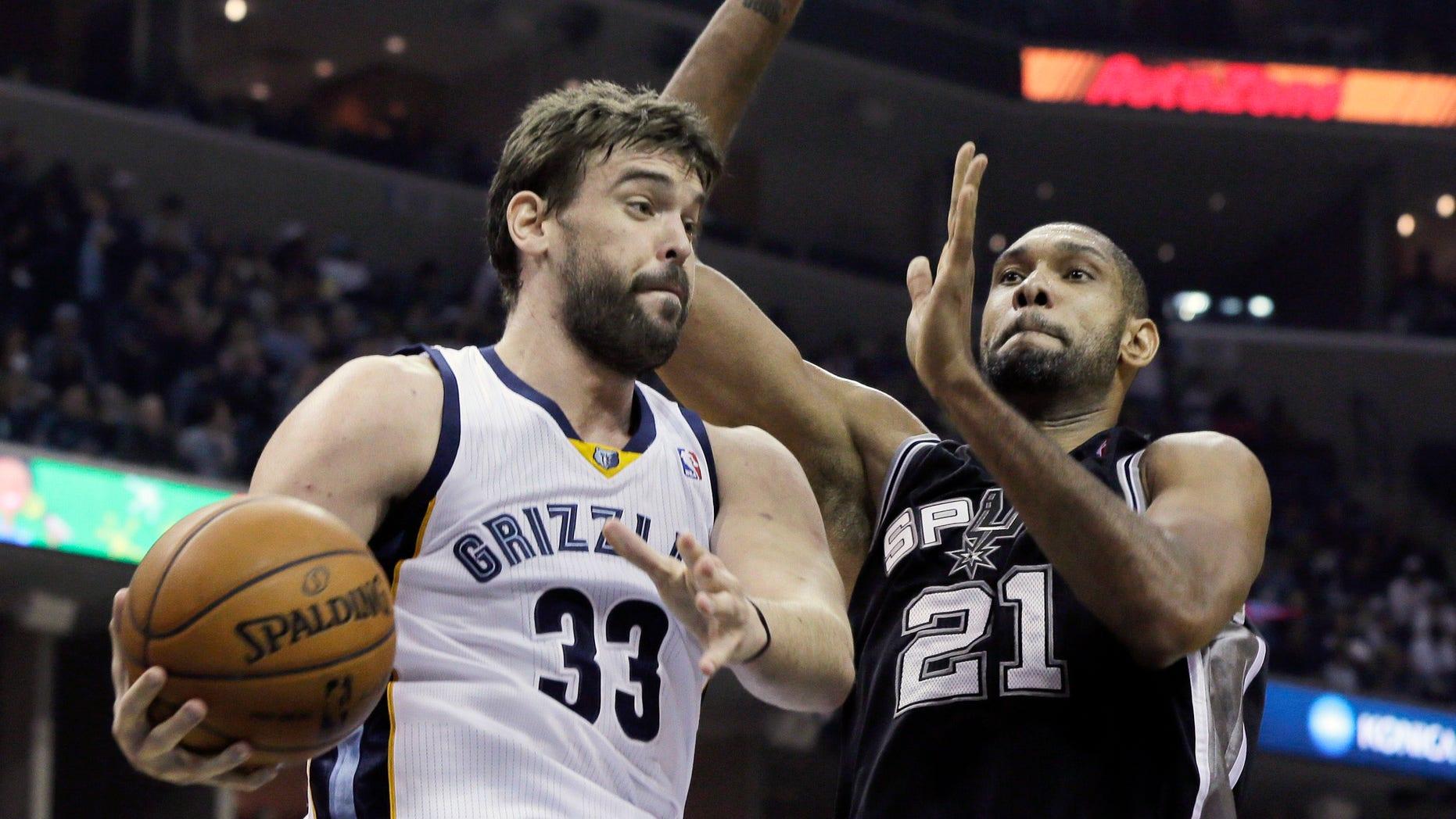 San Antonio Spurs' Tim Duncan (21), of U.S. Virgin Islands, defends against Memphis Grizzlies' Marc Gasol (33), of Spain, in the first half of an NBA basketball game in Memphis, Tenn., Friday, Nov. 22, 2013. (AP Photo/Danny Johnston)