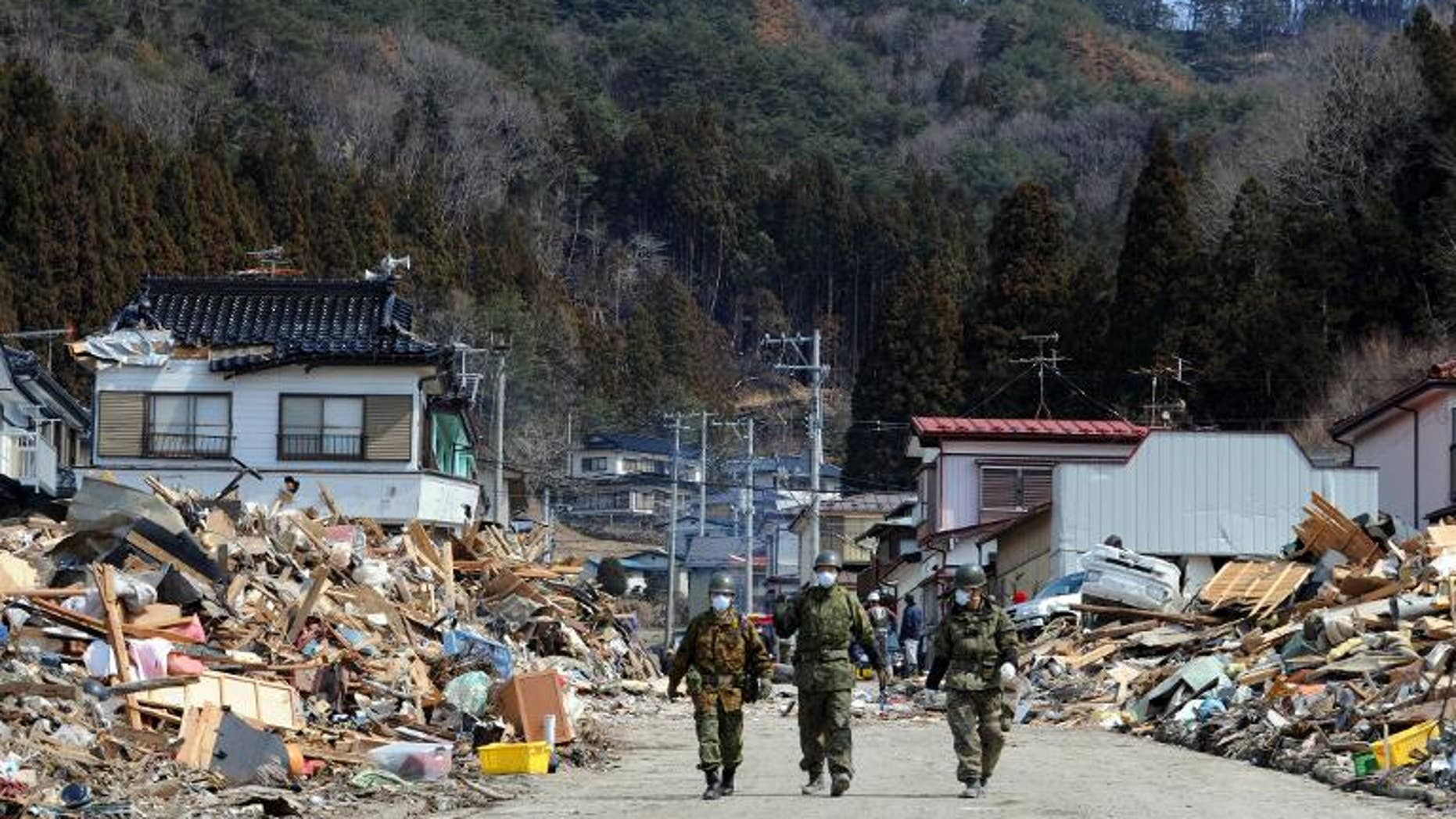 Japanese soldiers walk through the tsunami-destroyed town of Yamada, March 25, 2011. The government has suspended a senior official who blogged about the pointlessness of rebuilding tsunami-hit towns because they were populated mostly by old people.