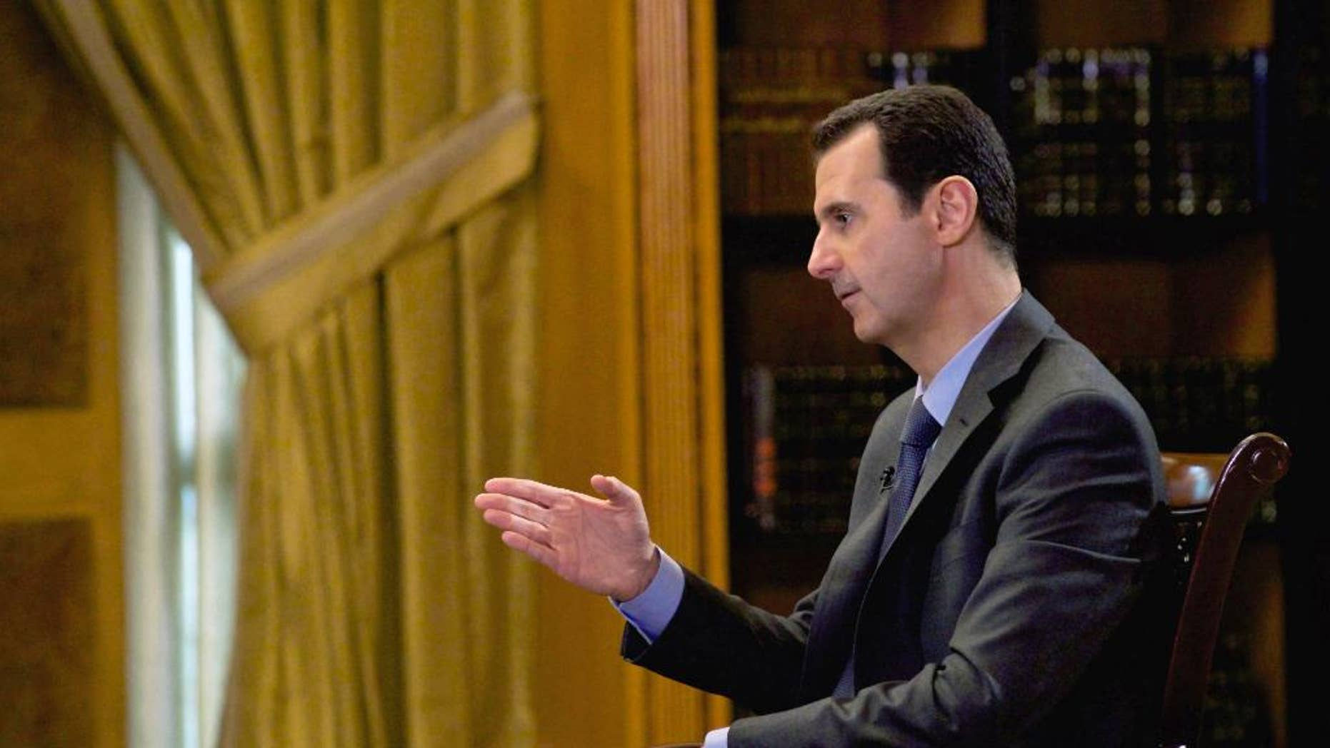 """In this photo released Wednesday, March 4, 2015, by the Syrian official news agency SANA, Syrian President Bashar Assad speaks during an interview with Portuguese state television, RTP, in Damascus, Syria. Assad denied that his troops drop barrels bombs on civilians telling a journalist: """"You are talking about massive propaganda."""" (AP Photo/SANA)"""