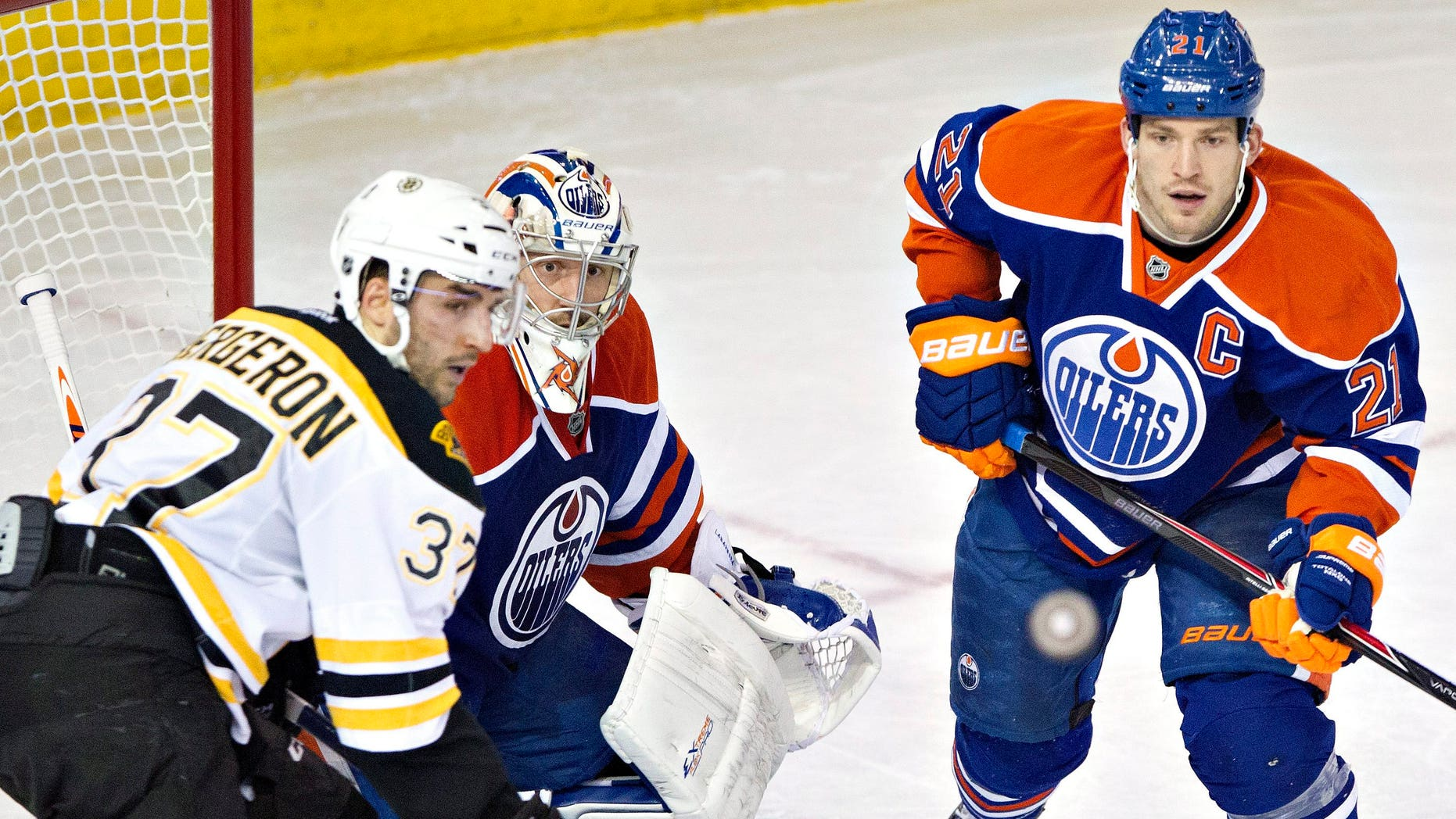 Boston Bruins' Patrice Bergeron (37), Edmonton Oilers goalie Jason LaBarbera (1) and Oilers' Andrew Ference (21) look for the rebound  during the second period of an NHL hockey game, Thursday, Dec. 12, 2013 in Edmonton, Alberta. (AP Photo/The Canadian Press, Jason Franson)