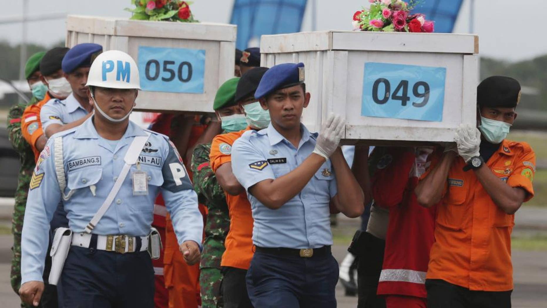 FILE - In this Monday, Jan. 19, 2015, file photo, members of the National Search and Rescue Agency carry coffins containing bodies of the victims aboard AirAsia Flight 8501 to transfer to Surabaya at the airport in Pangkalan Bun. The plane was climbing at an abnormally high rate, then plunged and suddenly disappeared from radar, Indonesia's transport minister said Tuesday, Jan. 20. (AP Photo/Achmad Ibrahim, File)