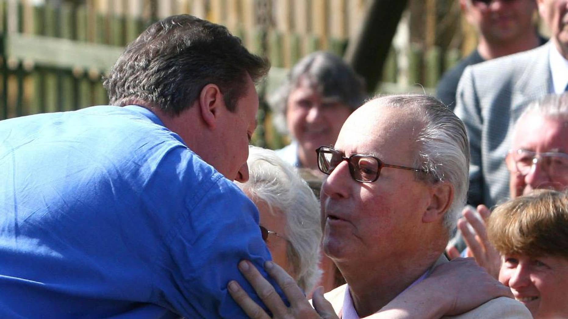 FILE - This is a  March 18, 2010 file photo of  Britain's Prime Minister David Cameron, left, as he  greets his father Ian Cameron, in Swindon England. British Prime Minister David Cameron was under pressure Tuesday April 4, 2016 to crack down on offshore tax havens, after a leak of millions of documents disclosed details of the asset-hiding arrangements of wealthy people including his late father. The Guardian newspaper revealed in 2012 that Ian Cameron, who died in 2010, used a Panamanian fund and other offshore investments to help shield investments from U.K. tax.  (Johnny Green/PA, File via AP) UNITED KINGDOM OUT