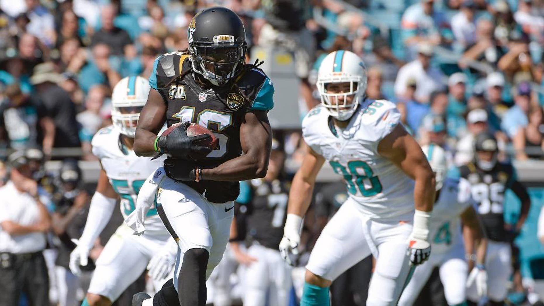 Jacksonville Jaguars running back Denard Robinson (16) takes off on a 41-yard run past Miami Dolphins defensive end Olivier Vernon, left, and defensive tackle Jared Odrick (98) during the first half of an NFL football game in Jacksonville, Fla., Sunday, Oct. 26, 2014. (AP Photo/Phelan M. Ebenhack)