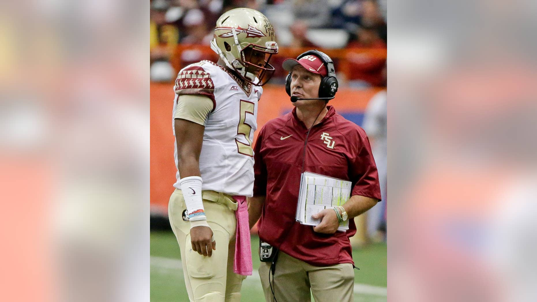 Florida State head coach Jimbo Fisher, right, talks to quarterback Jameis Winston (5) during the second half of an NCAA college football game against Syracuse, Saturday, Oct. 11, 2014, in Syracuse, N.Y. Florida State won the game 38-20. (AP Photo/Frank Franklin II)