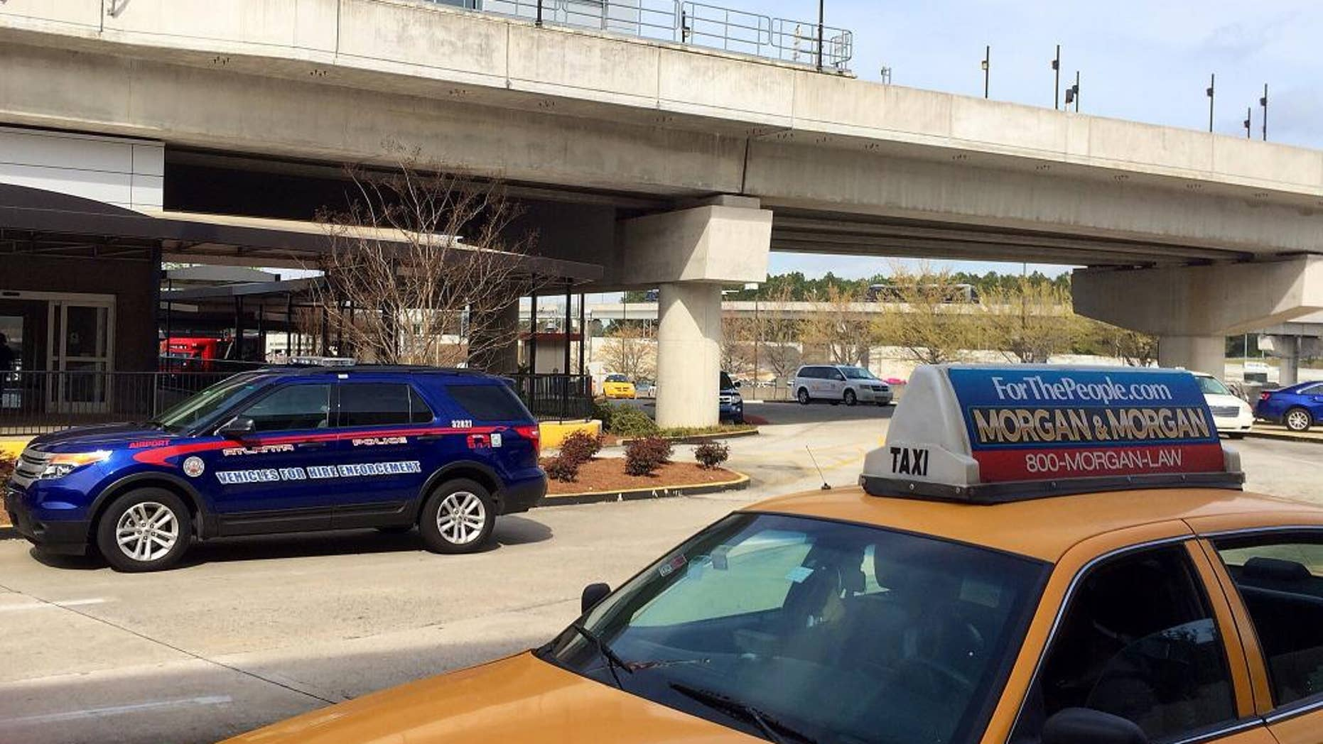 In this March 25, 2016 photo, an Atlanta Police Rides-For-Hire Enforcement vehicle sits amid taxi cabs outside the departures area of the domestic terminal at Hartsfield-Jackson Atlanta International Airport. A battle over background checks for Uber drivers at the world's busiest airport comes as cities like Los Angeles and Austin, Texas, consider more thorough screenings to prevent criminals from getting behind the wheel. Uber has objected to the use of fingerprints to check criminal records of its drivers, saying its own record checks are sufficient. (AP Photo/Jeff Martin)