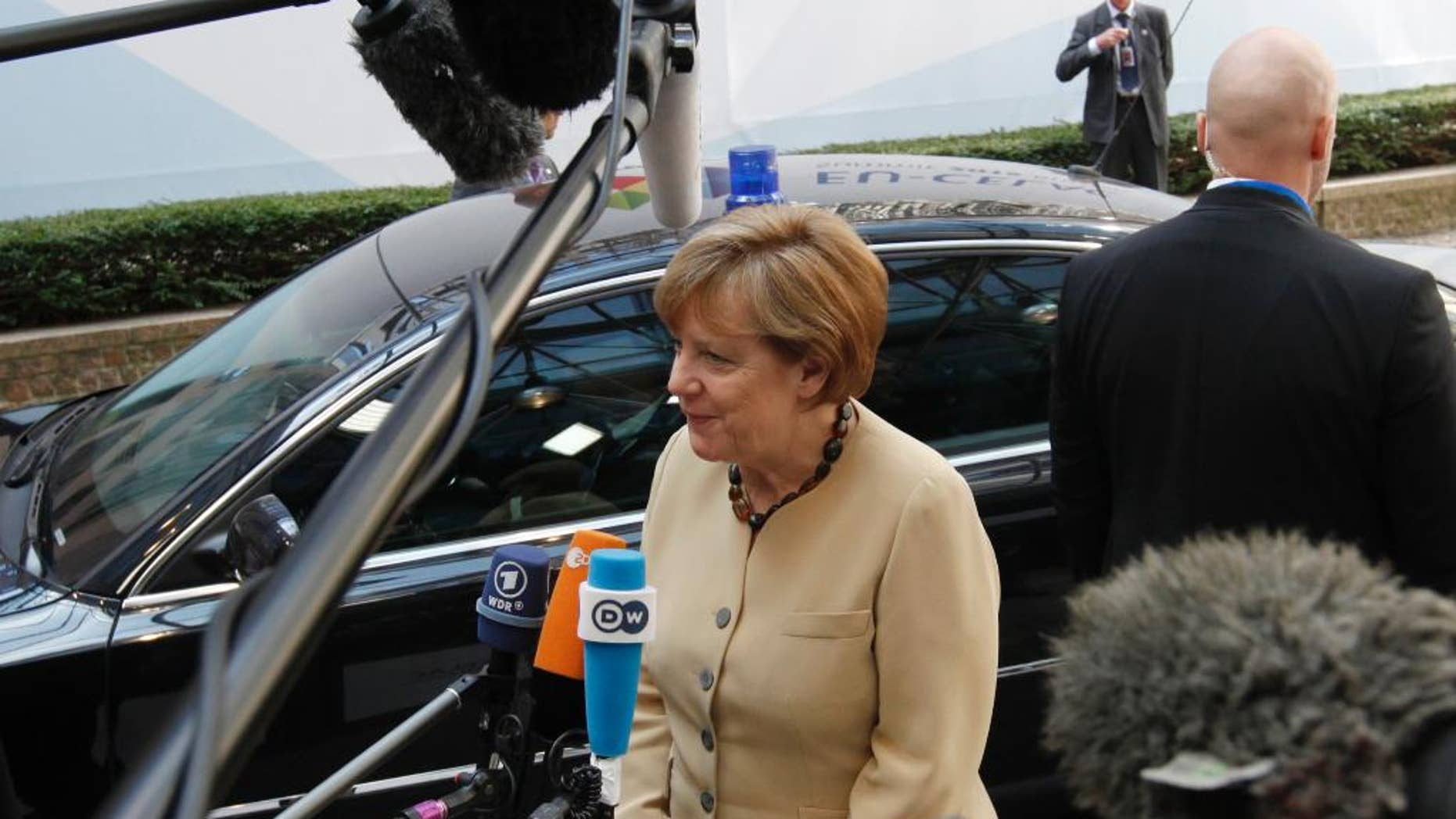 German Chancellor Angela Merkel, center, speaks with the media as she departs an EU-CELAC summit in Brussels on Thursday, June 11, 2015. The main aim of the Brussels summit was to boost trade and diplomatic ties with the region. (Geert Vanden Wijngaert)